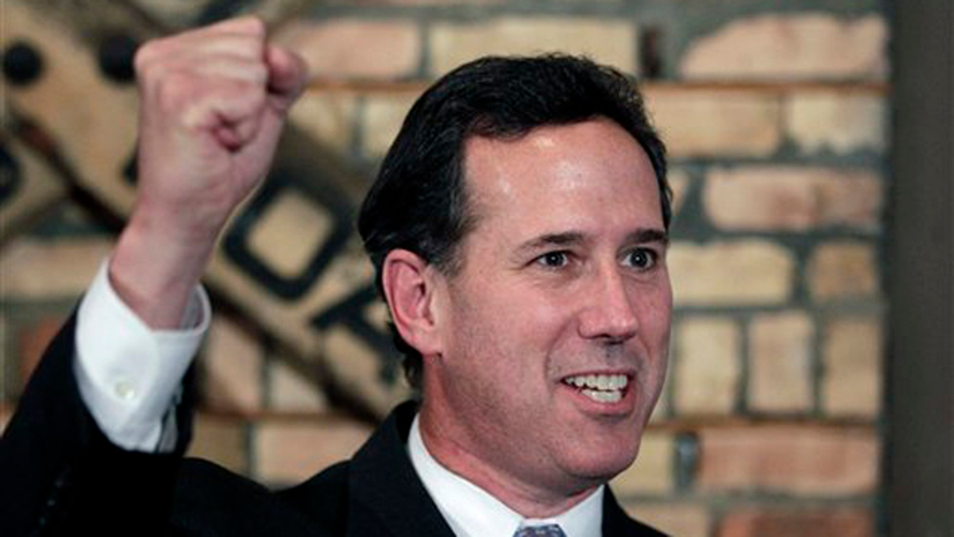 March 24, 2012: Rick Santorum pumps his fist while talking to reporters during a news conference in Green Bay, Wis.