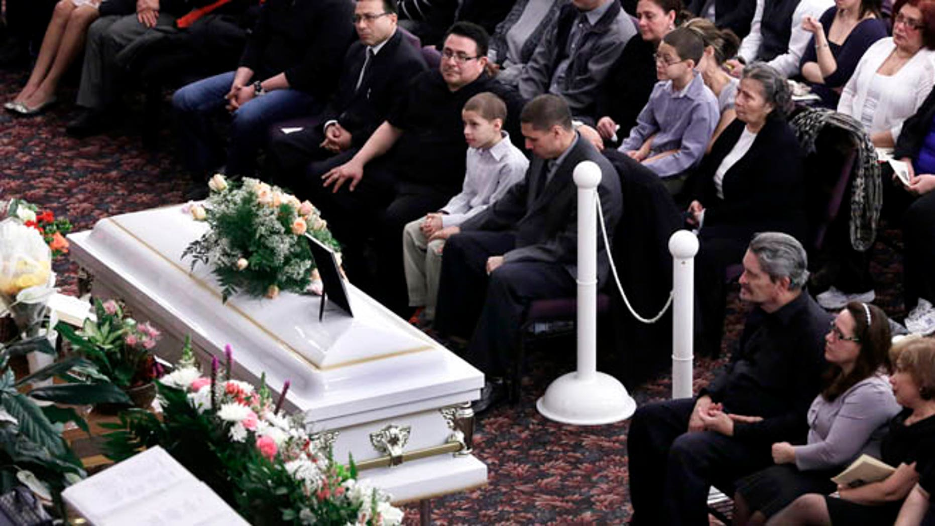 Feb. 15, 2013: Steven Sierra, husband of Sarai Sierra, upper center, with his son Silas Sierra, age 9, and Dennis Jimenez, second from right, father of Sarai Sierra, with his wife Betzaida Jimene, attend her funeral, at the Christian Pentecostal Church, in the Staten Island borough of New York.  The 33-year-old mother of two was killed while vacationing alone in Turkey. Her body was found in Istanbul, 12 days after she disappeared.