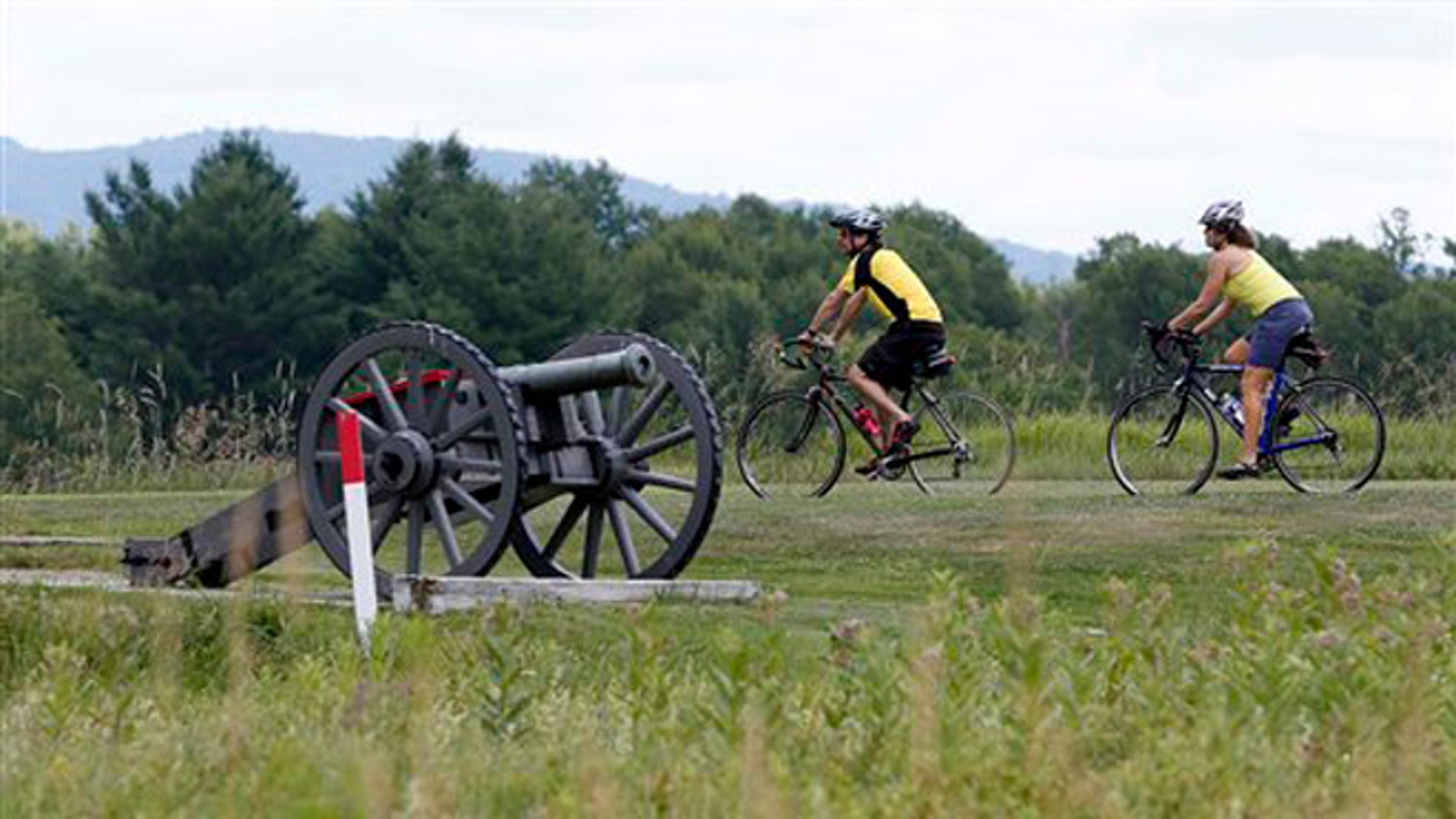 July 2, 2012: Eric Epstien, left, and Isabelle Davidowitz, of Braddock Heights, Md., ride past a cannon on a bike tour of Saratoga National Historical Park in Stillwater, N.Y.