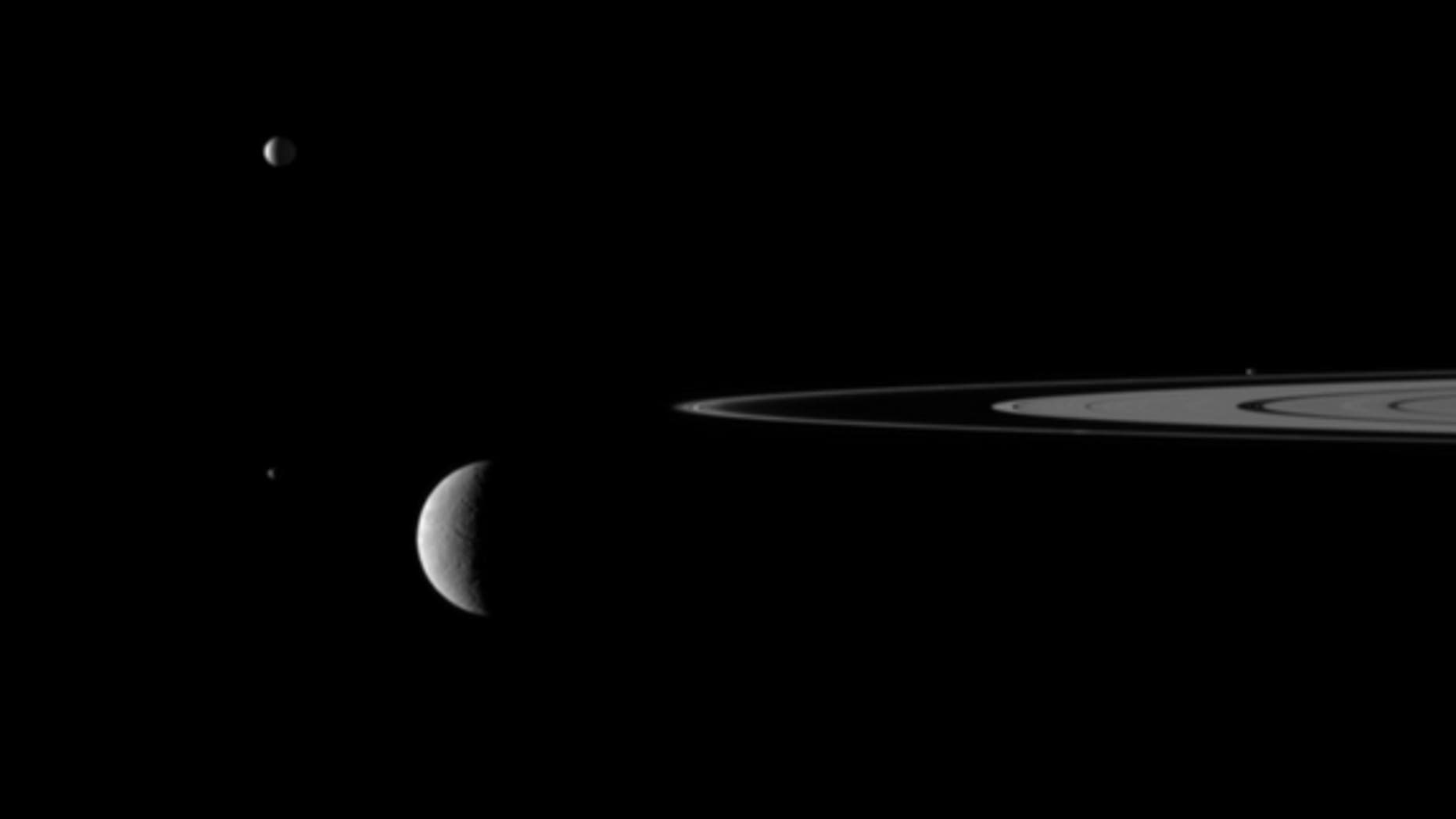 """This still from the video """"Outer Space"""" shows Saturn's rings and four of the giant planet's moons."""