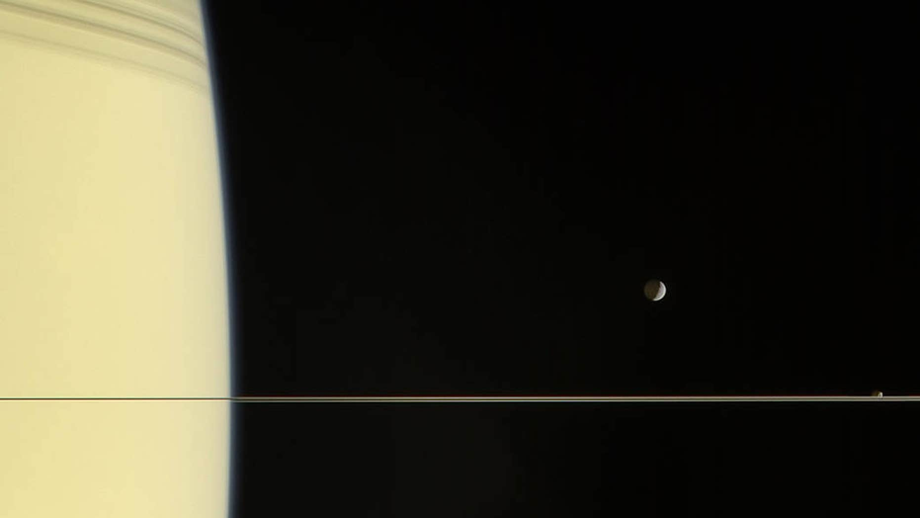 NASA's Cassini spacecraft captured this image of Saturn, its rings and the moons Mimas, Janus and Tethys on March 13, 2006. Tethys is below the ring plane, Mimas is above it and tiny Janus appears to sit right on the rings in this view.