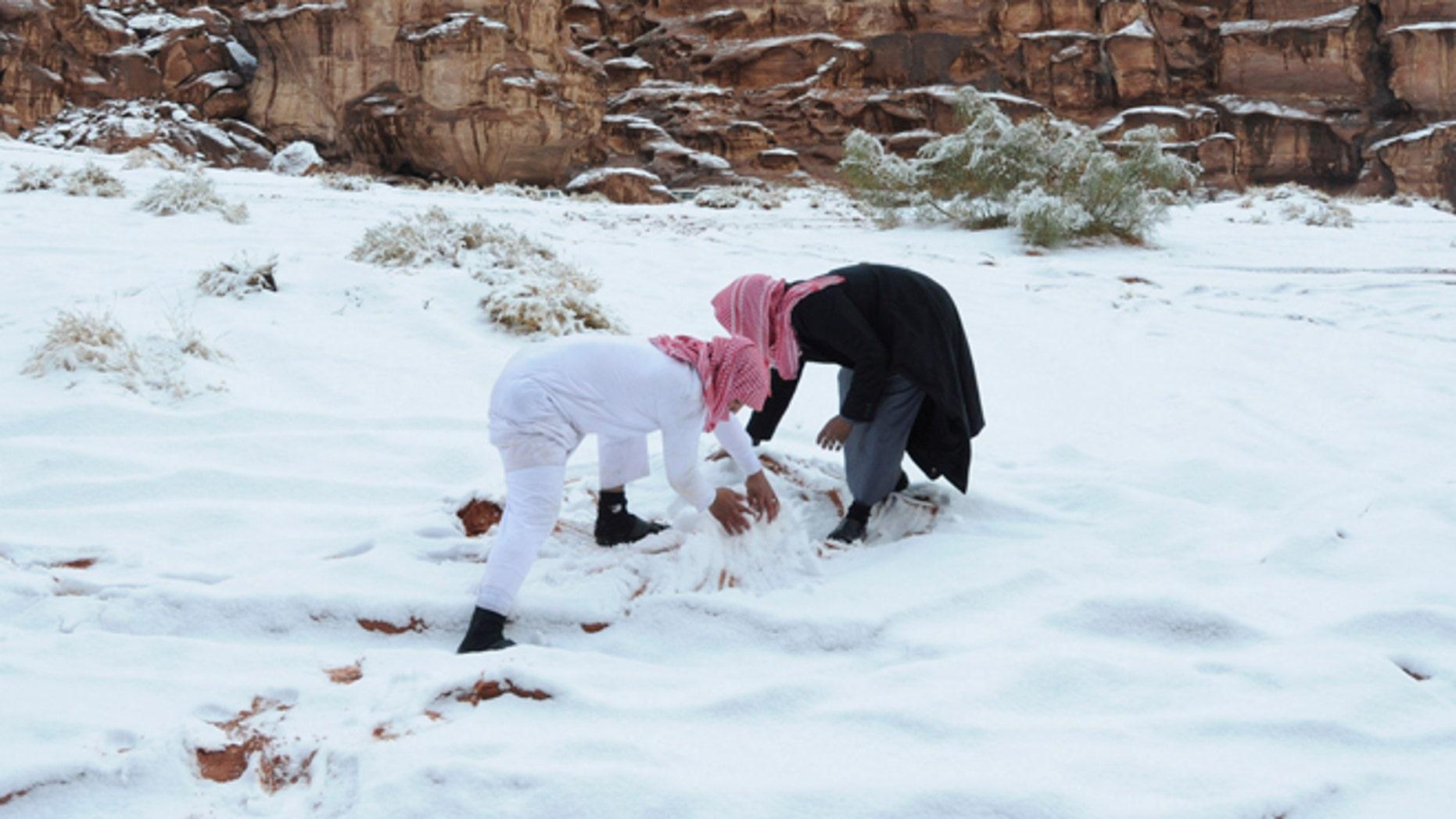 Dec. 13, 2013: Saudi men make a snowman after a snowstorm in Alkan village, west of Saudi Arabia.