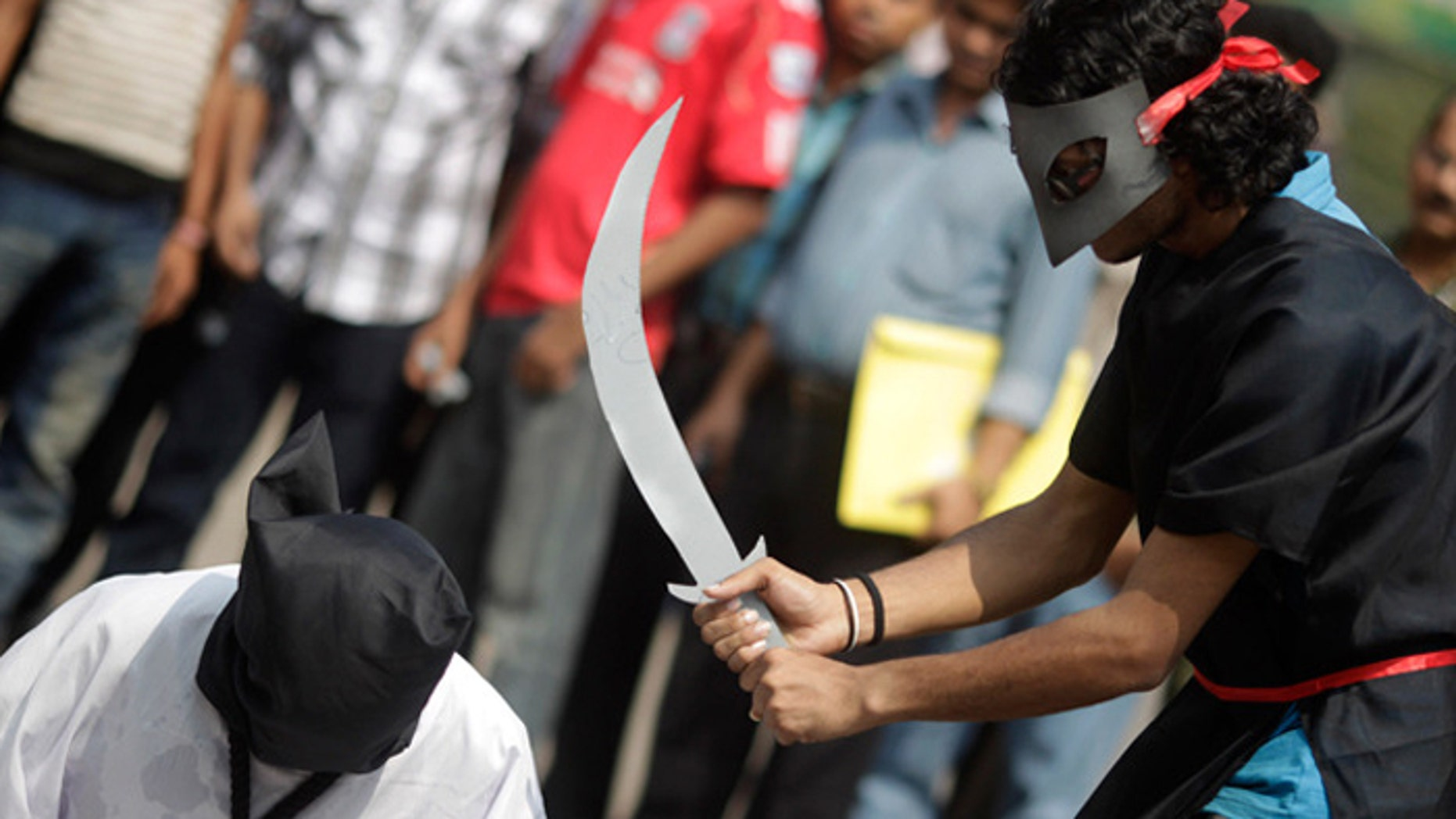 Demonstrators stage a mock beheading to protest executions in Saudi Arabia (Reuters)