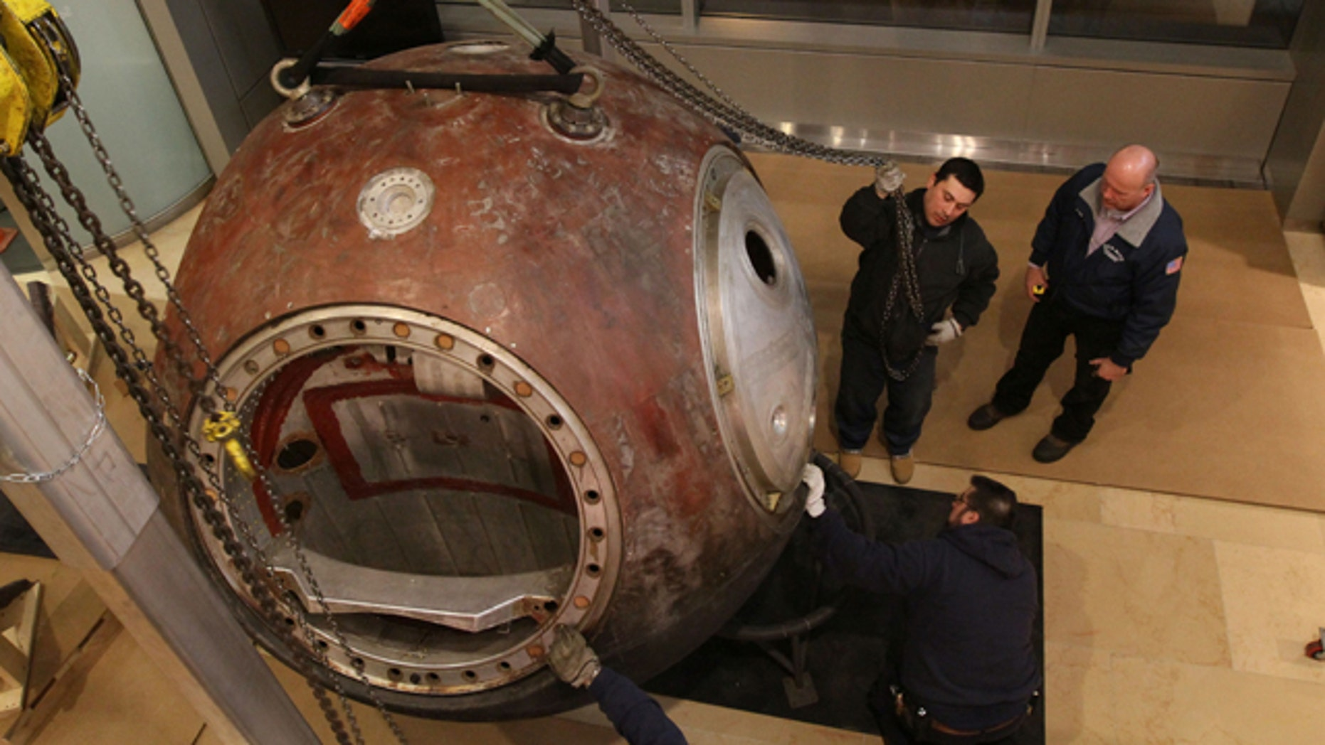 Workers move the Vostok 3KA-2 space capsule into place for display at Sotheby's in New York.