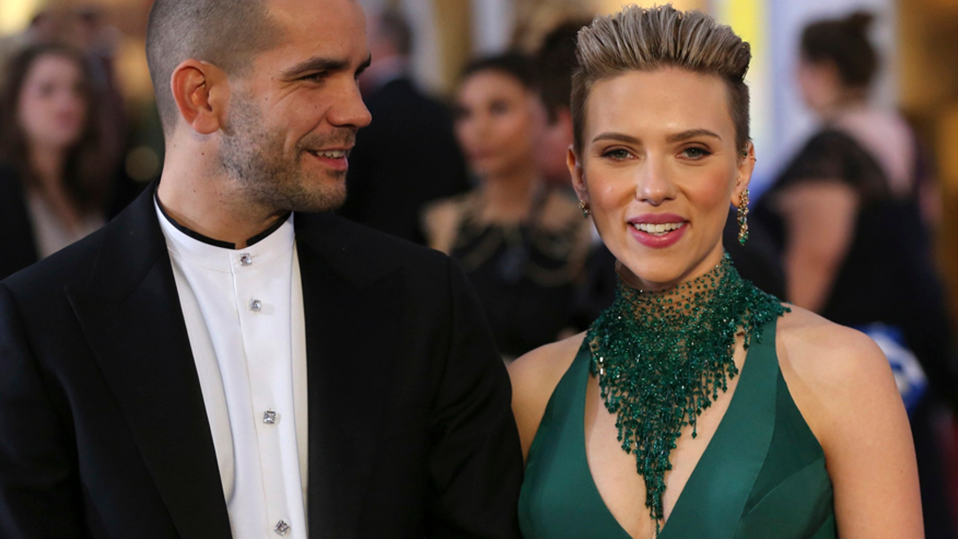 Actress Scarlett Johansson wears a Versace dress as she and then-husband Romain Dauriac arrive at the 87th Academy Awards in Hollywood, California February 22, 2015.