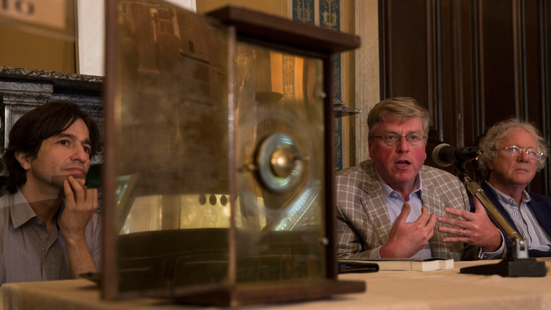 June 9, 2016: Alexander Jones, center, Mike Edmunds, right, and Yanis Bitsakis sit behind a possible reconstruction of the more than 2,000-year-old Antikythera Mechanism during a press conference in Athens