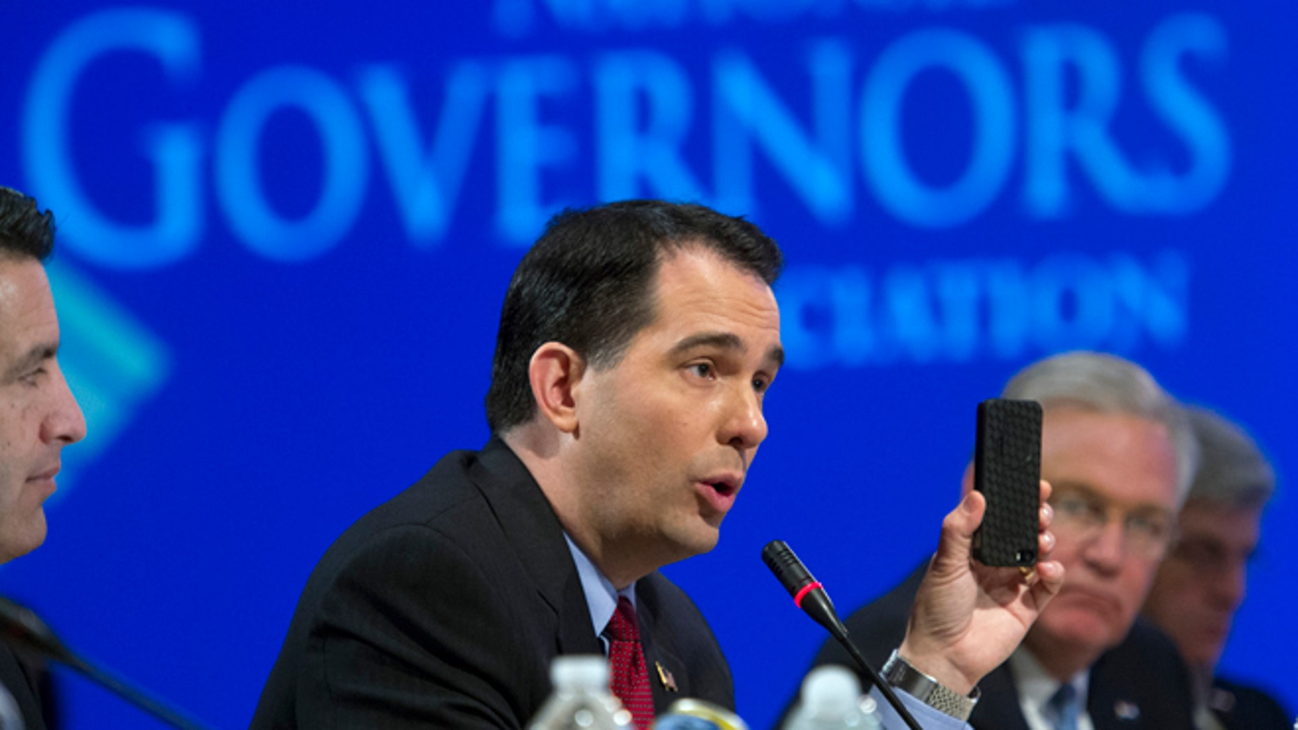 Feb. 23, 2014: Wisconsin Gov. Scott Walker uses a cellphone to illustrate a point about health care plans during a special session on jobs in America during the National Governor's Association Winter Meeting in Washington.