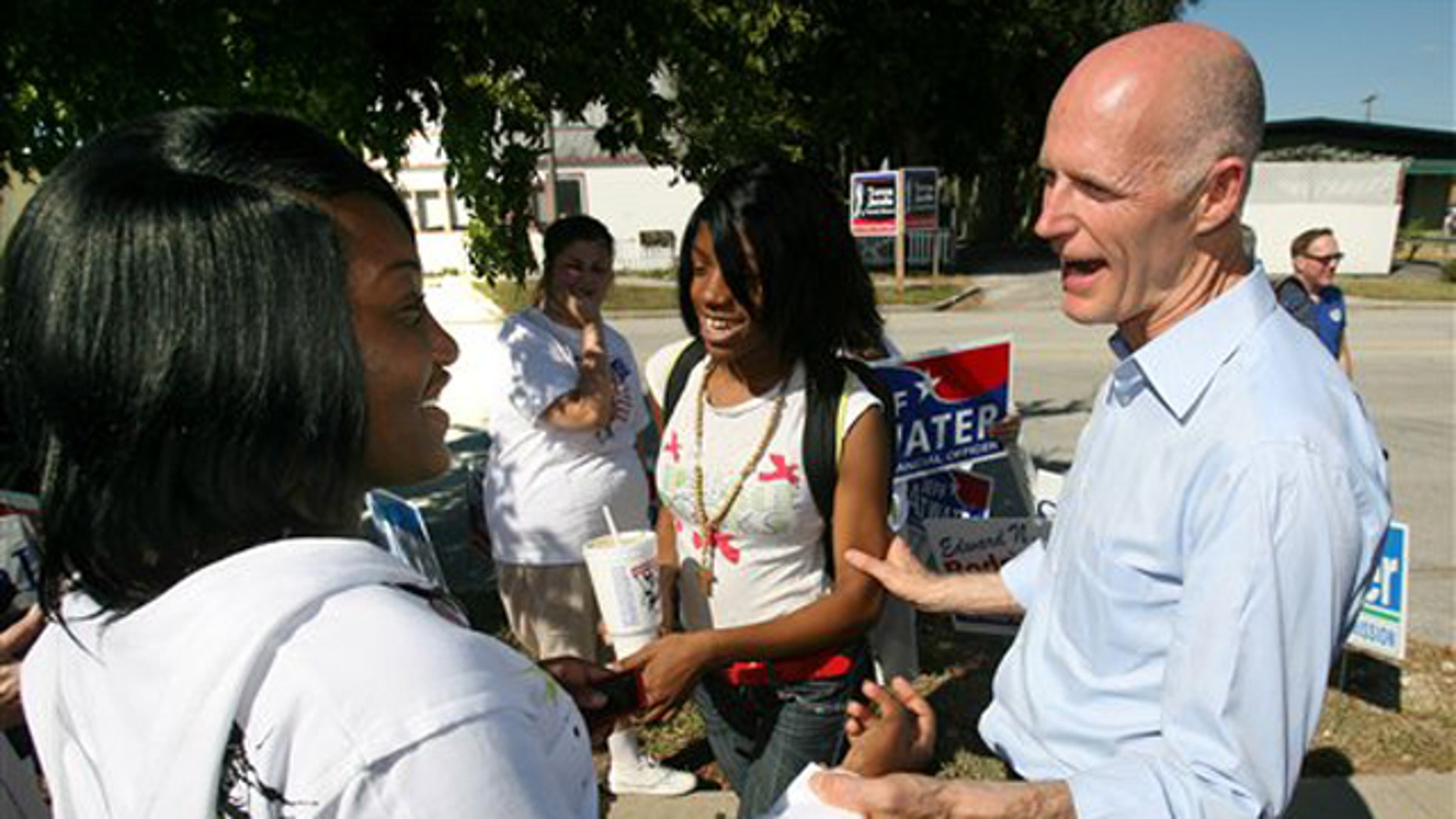 Republican gubernatorial nominee Rick Scott talks to young supporters during a campaign stop at the VFW post in Apopka, Fla., on the first day of early voting Oct. 18. (AP Photo)