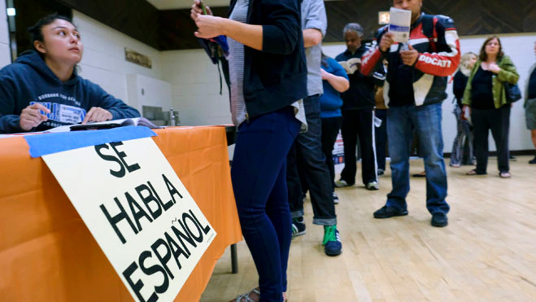 """A sign that reads """"Spanish is Spoken Here"""" hangs as voters check in at the North Hollywood Amelia Earhart Regional Library polling station in Los Angeles on Tuesday, Nov. 8, 2016. (AP Photo/Richard Vogel)"""