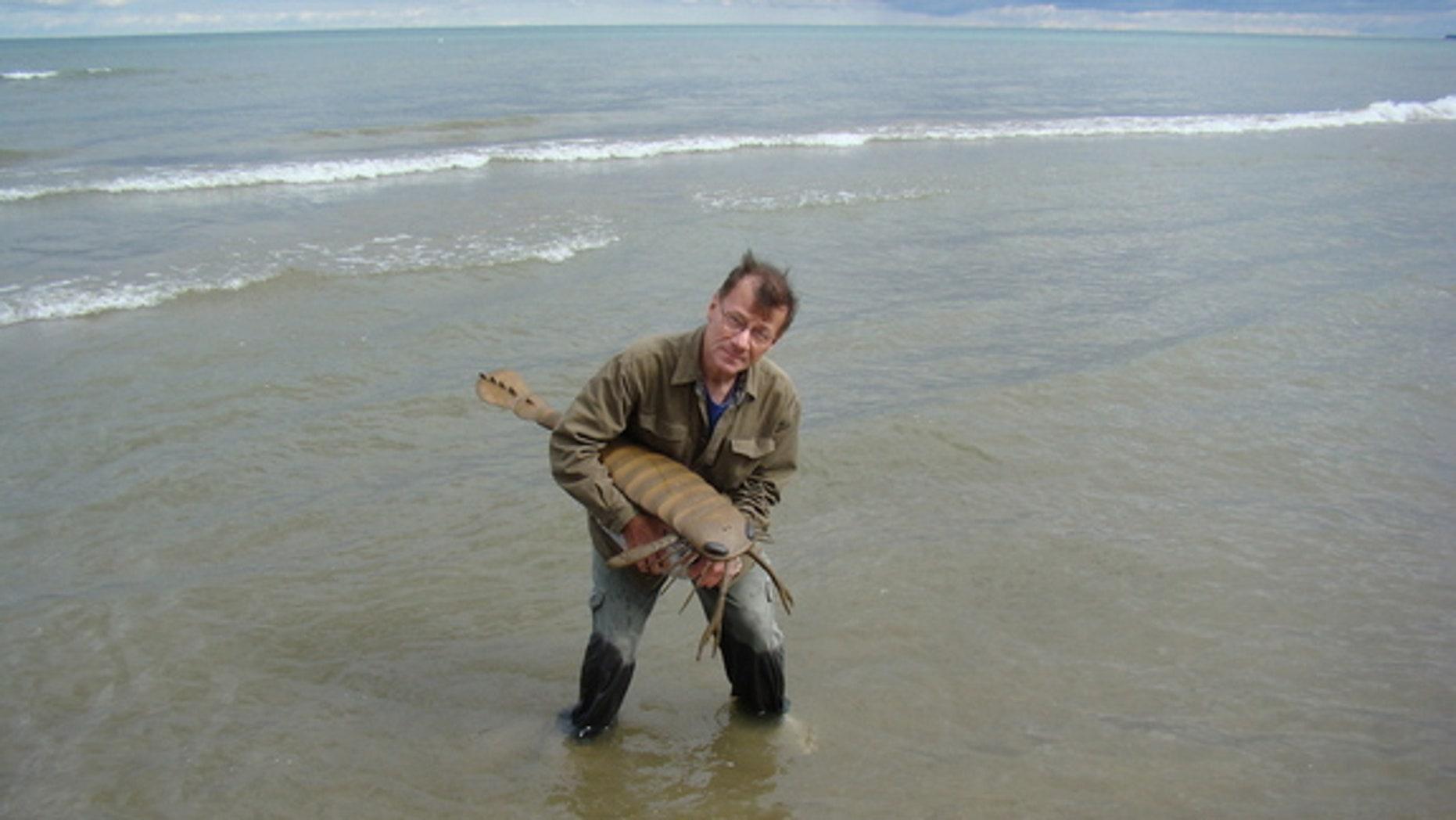 Sam Ciurca, who collected the sea scorpion specimens, with a life size model of one called Acutiramus.