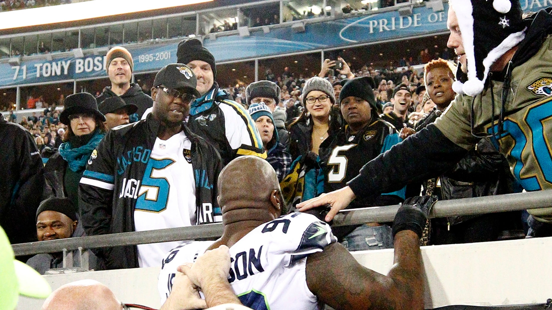 Dec. 10: Seattle Seahawks defensive tackle Quinton Jefferson tries to climb up in the stands after a fan threw an object in his direction.
