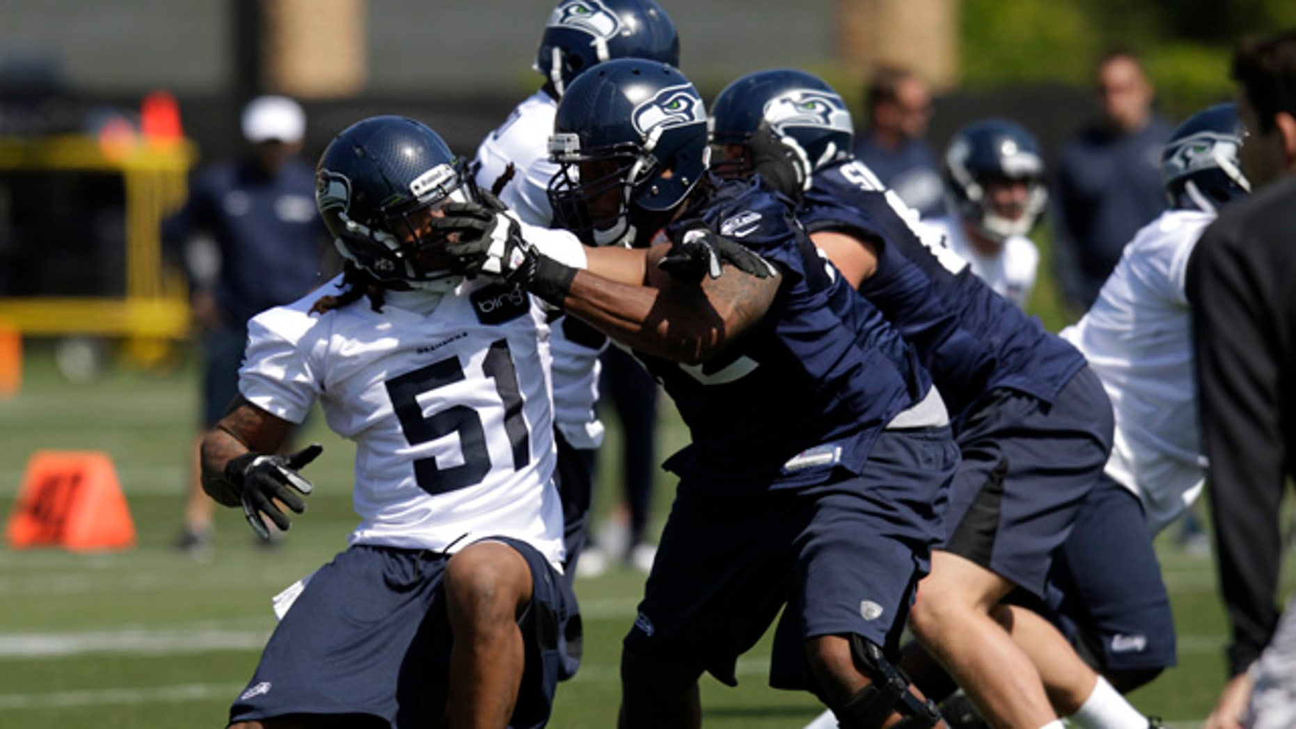 May 11, 2012: Bruce Irvin (51), the Seattle Seahawks' top NFL draft pick, tangles with Seahawks tackle Alex Barron, front right, during an NFL football rookie minicamp in Renton, Wash. (AP/Ted S. Warren)