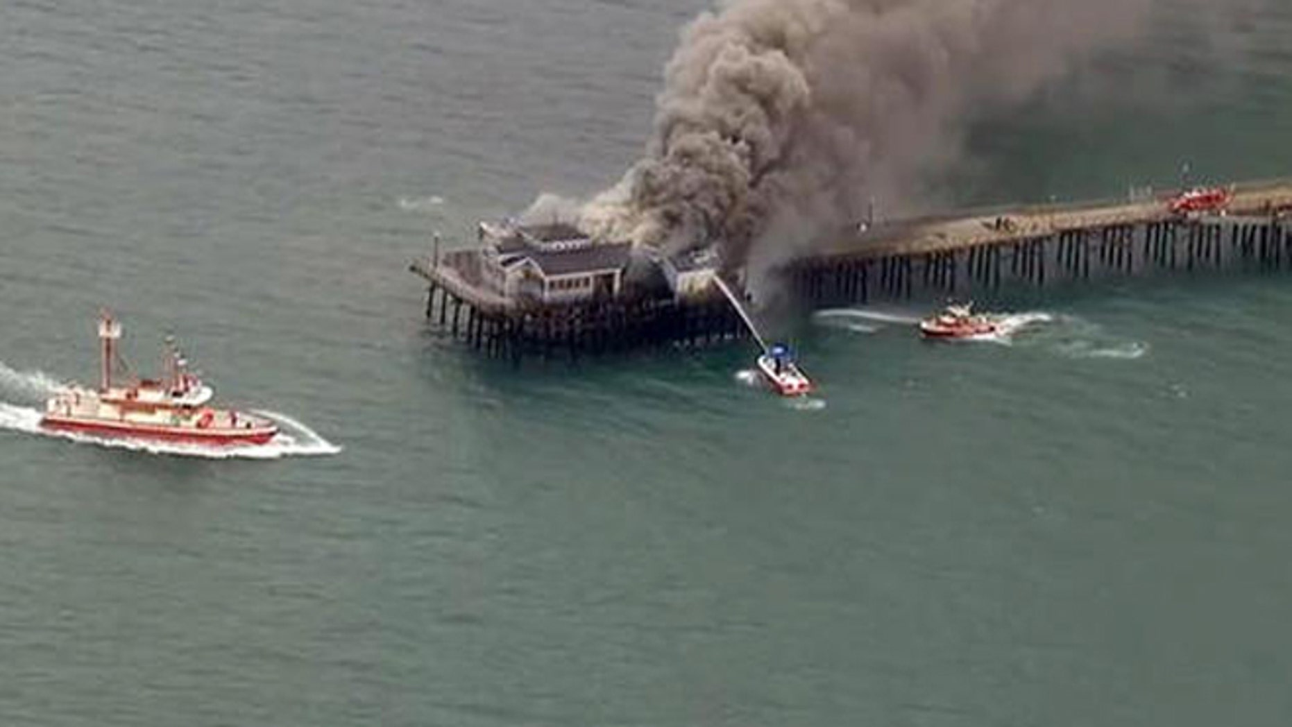 Firefighters attack a fire on the Seal Beach pier in Seal Beach, Calif. on Friday, May 20, 2016. (KABC-TV via AP)