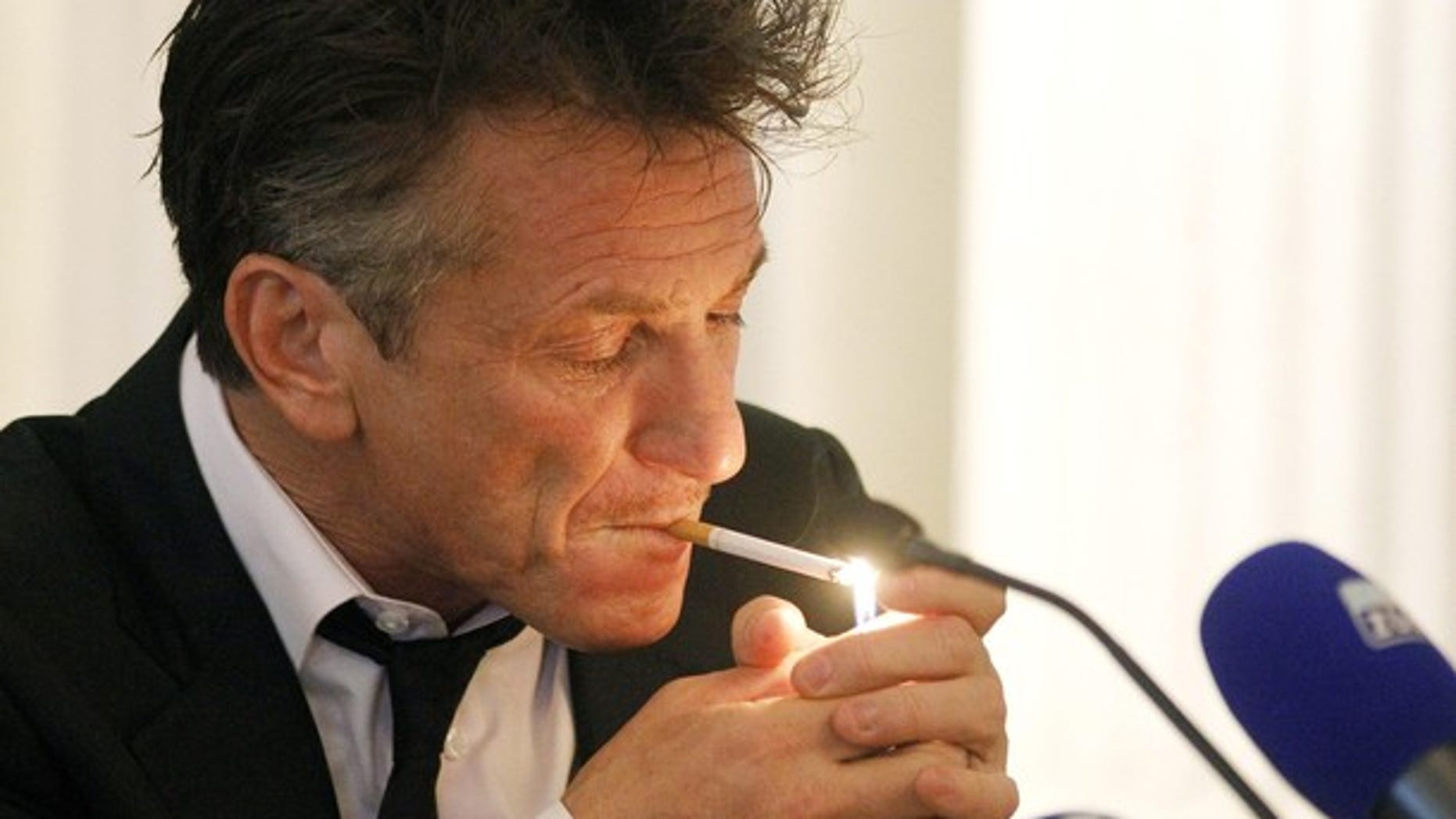 U.S. actor and director Sean Penn lights a cigarette during a news conference at the Zurich Film Festival in Zurich September 28, 2011.