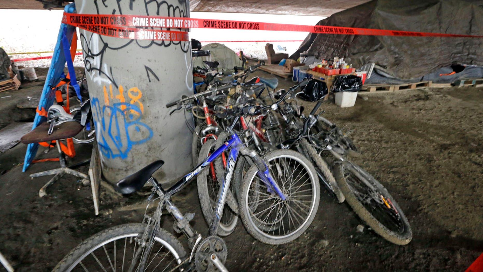 Jan. 27, 2016: Bicycles remain stacked against a support post for Interstate 5 above as crime scene tape surrounds the site of a shooting the night before at a homeless encampment in Seattle. (AP Photo/Elaine Thompson)