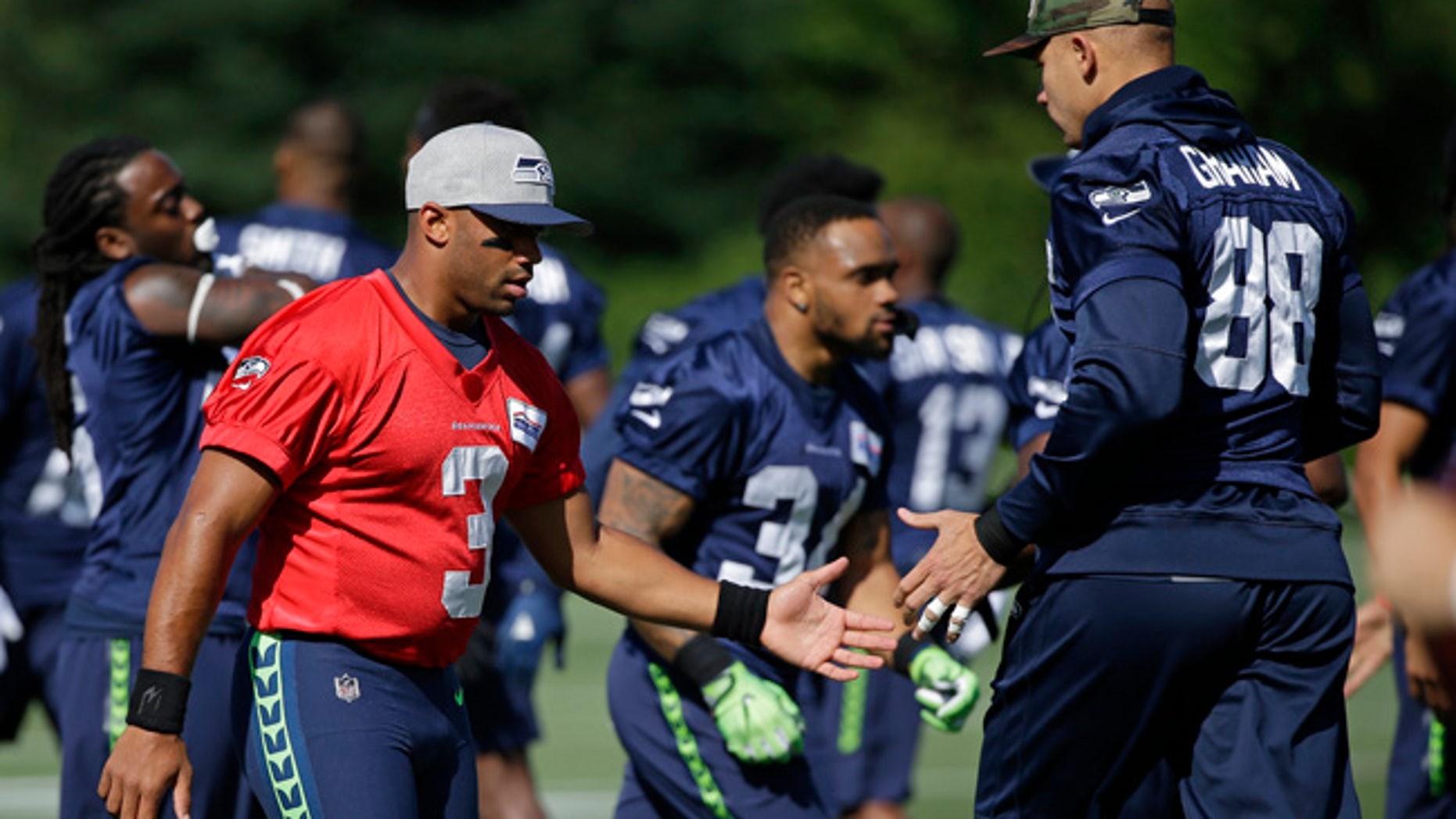 Seattle Seahawks quarterback Russell Wilson, left, greets tight end Jimmy Graham (88) at NFL football training camp, Sunday, July 30, 2017, in Renton, Wash. (AP Photo/Ted S. Warren)