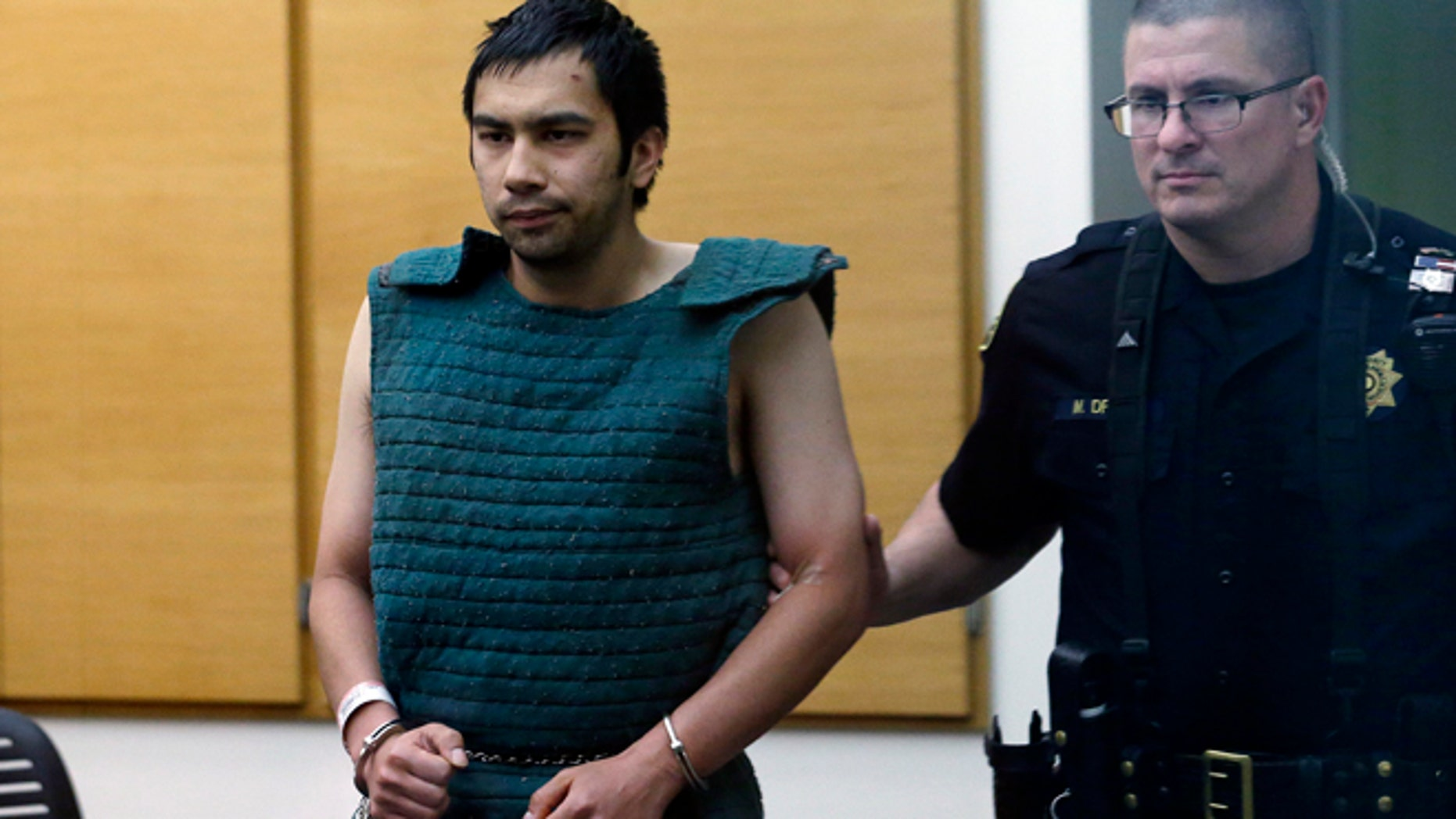 June 6, 2014: Shooting suspect Aaron Ybarra, left, is led in chains to a court hearing at a King County Jail in Seattle.
