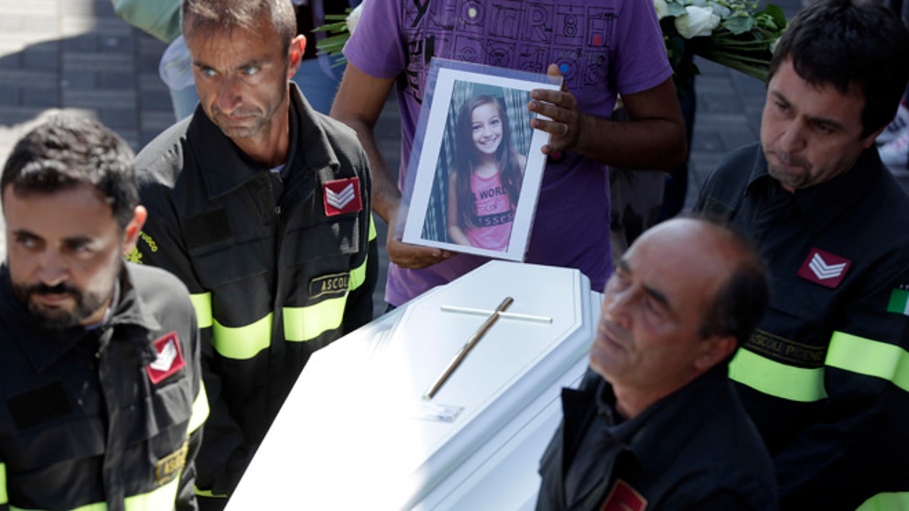 The coffin of Giulia, 9 years old, is carried outside the gymnasium at the end of the state funeral service in Ascoli Piceno, Italy,.