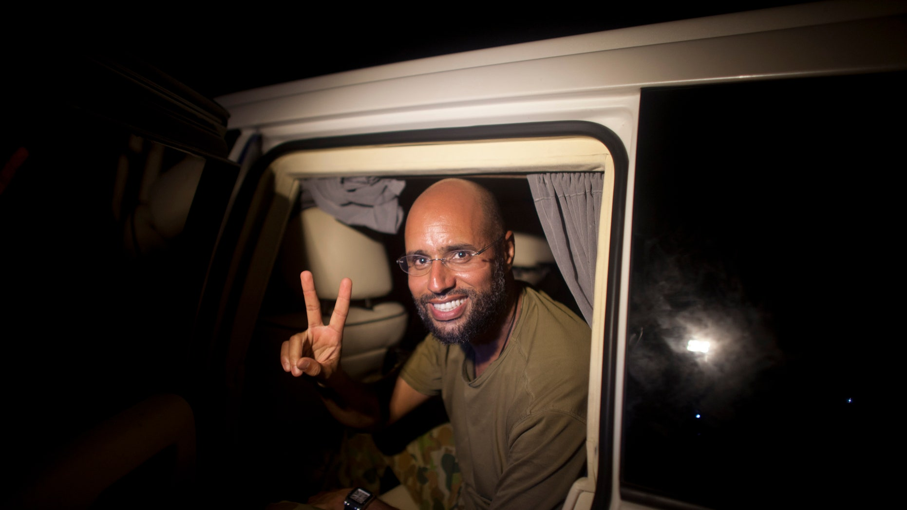 In this Tuesday, Aug. 23, 2011 file photo, Muammar Qaddafi's son Seif al-Islam makes a victory sign as he appears at the Rixos hotel in Tripoli, Libya. A Libyan commander told reporters Saturday, Nov. 19, 2011 that Seif al-Islam Gadhafi has been arrested in south Libya.