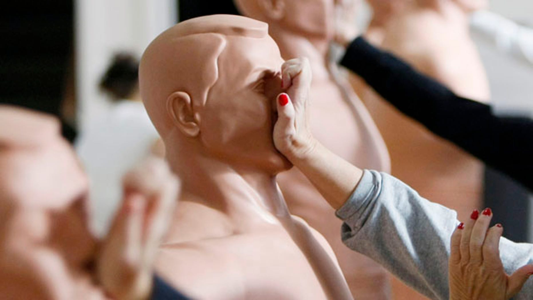 Women practice strikes against rubber mannequins during a self-defense course in Denver.
