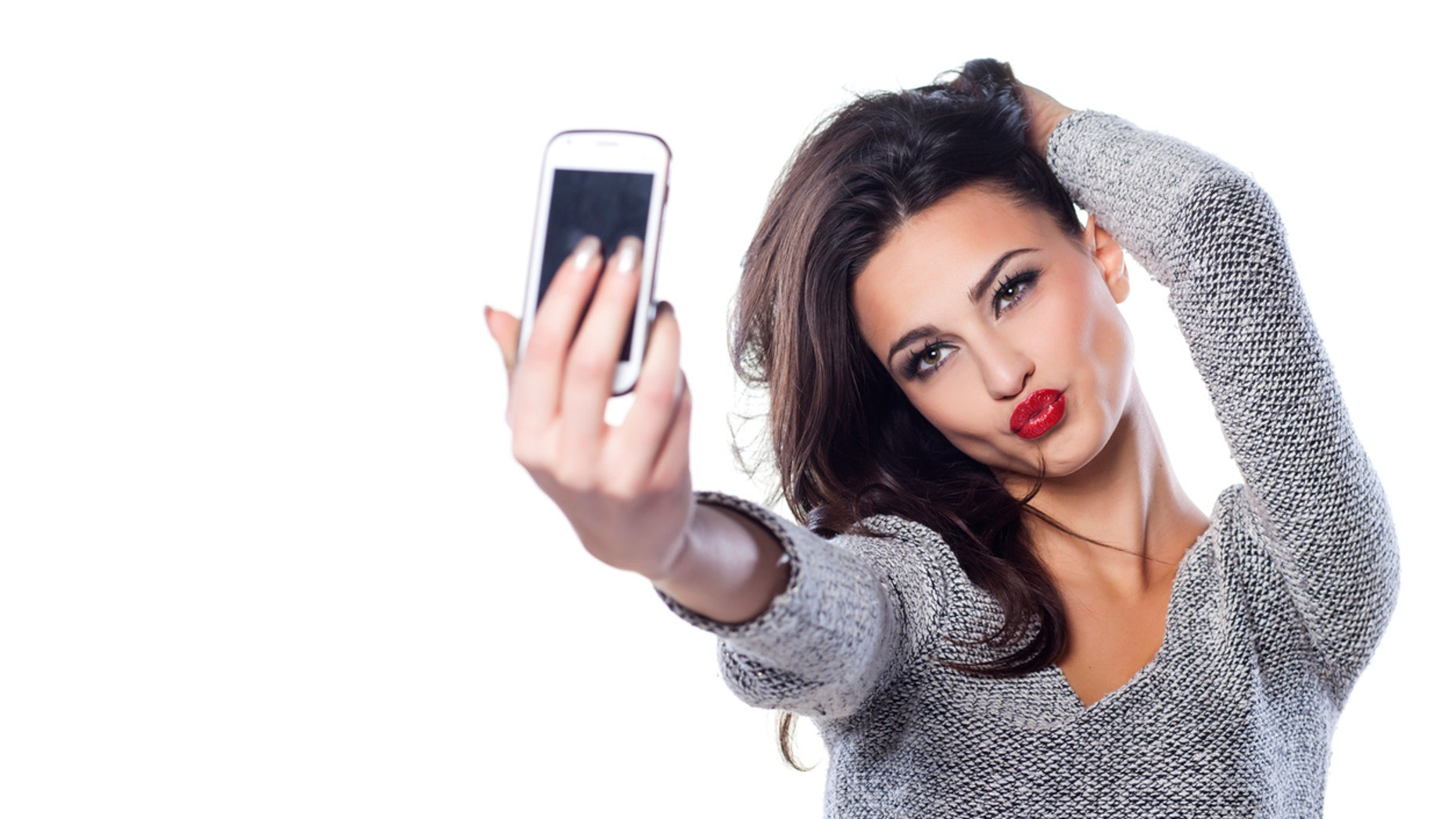 pretty girl make a duck face, and take a self portrait with her smart phone