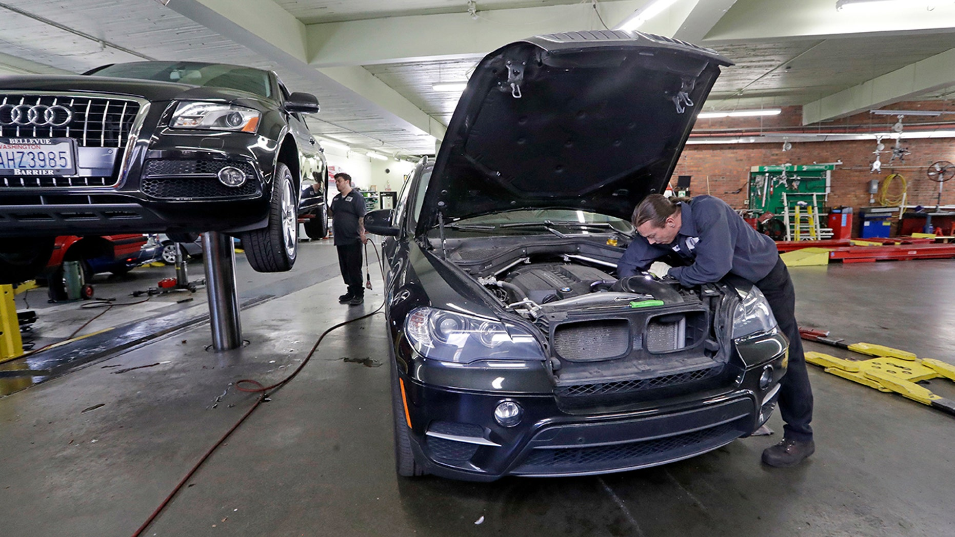 In this Wednesday, April 25, 2018, photo, auto technician Anthony Sterns, right, works to replace the coolant expansion tank on a 2011 BMW at the Fat City German Car service shop in Seattle. At first, dumping your old car might seem like a no-brainer, and you can't help picturing how good you would look in that new car. But automotive experts say you'll almost always come out ahead, at least financially, by fixing old faithful. (AP Photo/Elaine Thompson)