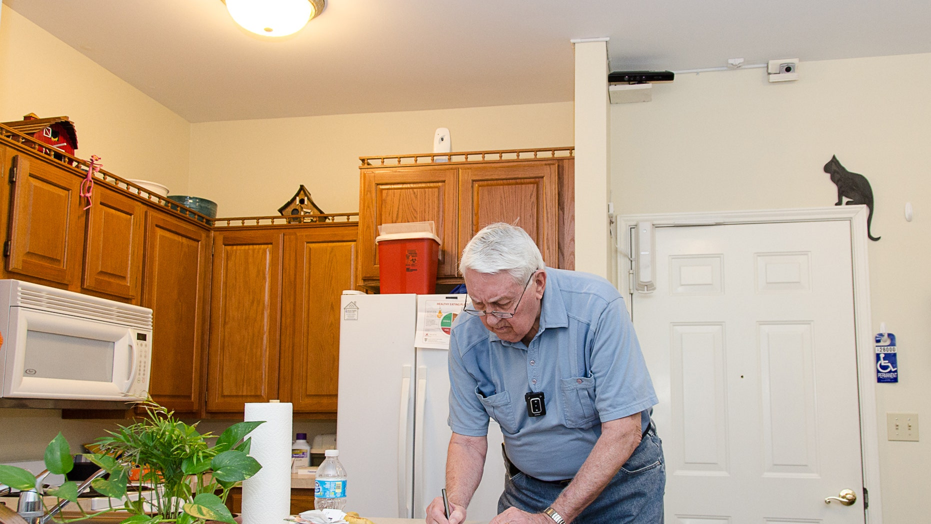 Bob Harrison writes in his TigerPlace apartment in Columbia, Mo., as different sensors mounted near the ceiling record activity patterns. The sensor technology is unobtrusive and does not interfere with his everyday tasks.