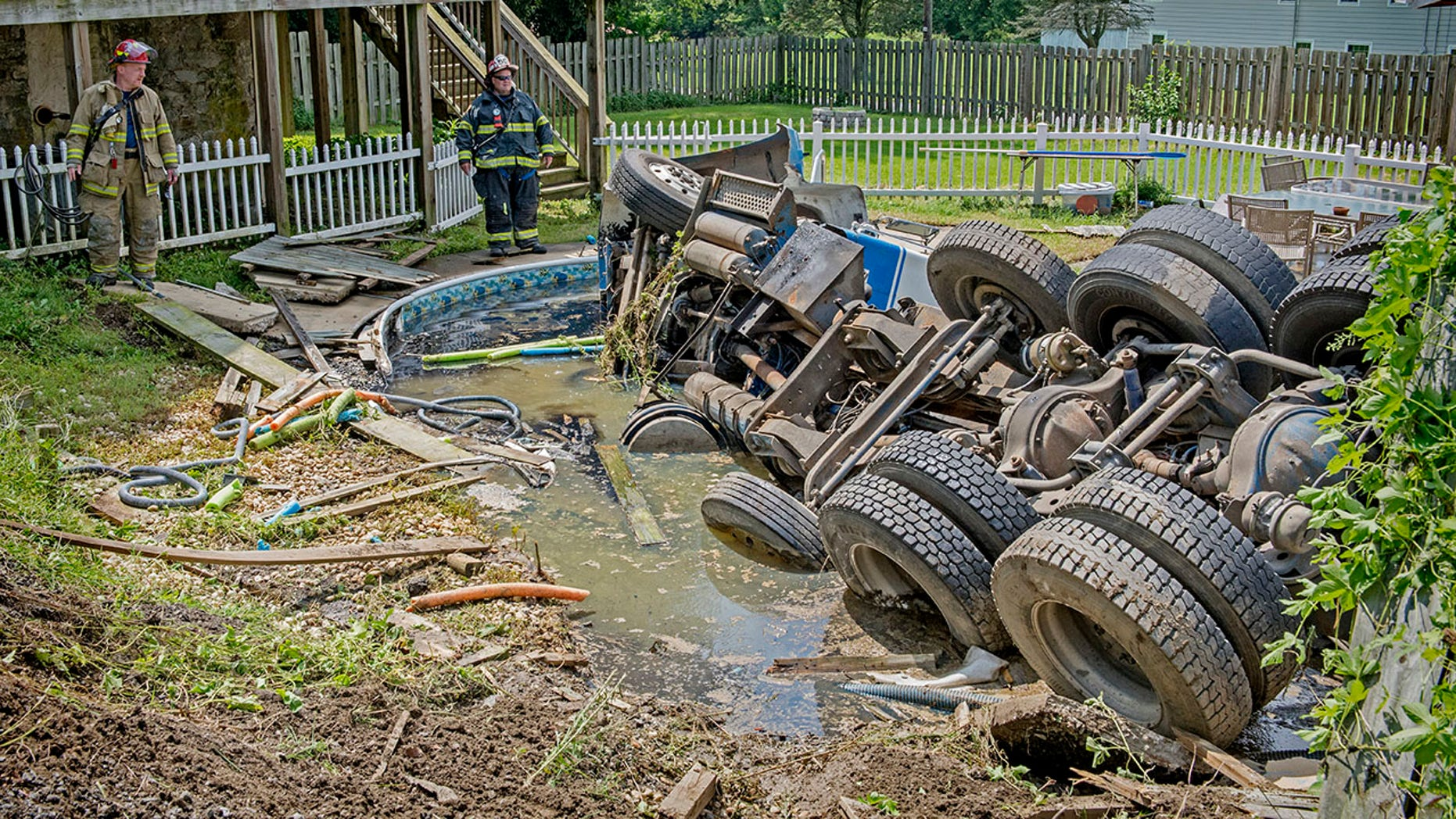 A septic truck overturned and crashed into a swimming pool Thursday, Aug. 9, 2018, on Slackwater Road at Stehman Road in Conestoga Township, Lancaster County, Pa.  (Blaine Shahan/LancasterOnline via AP)
