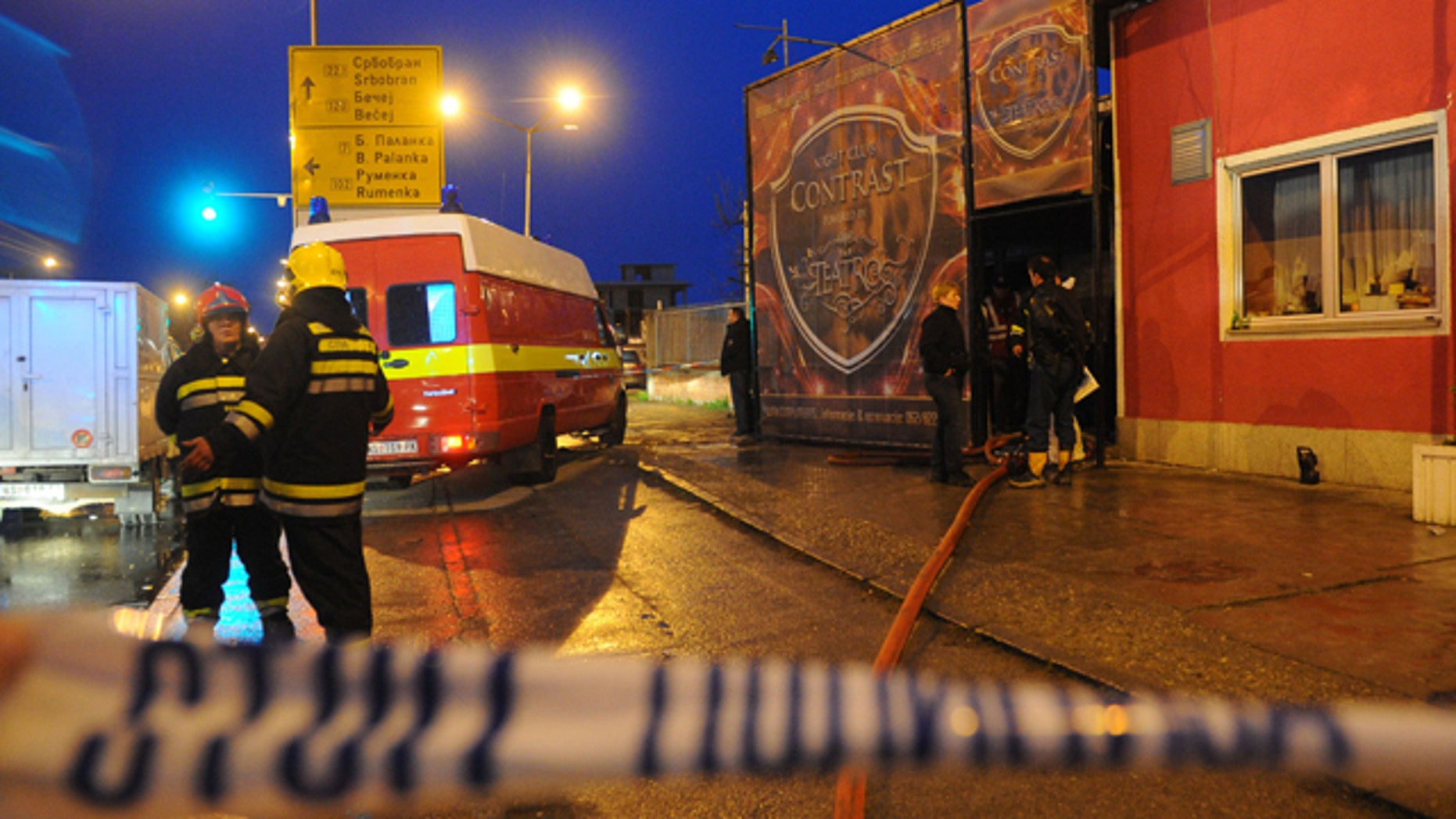 April 1, 2012: Firefighters stand in front of the nightclub Contrast in Novi Sad, Serbia.