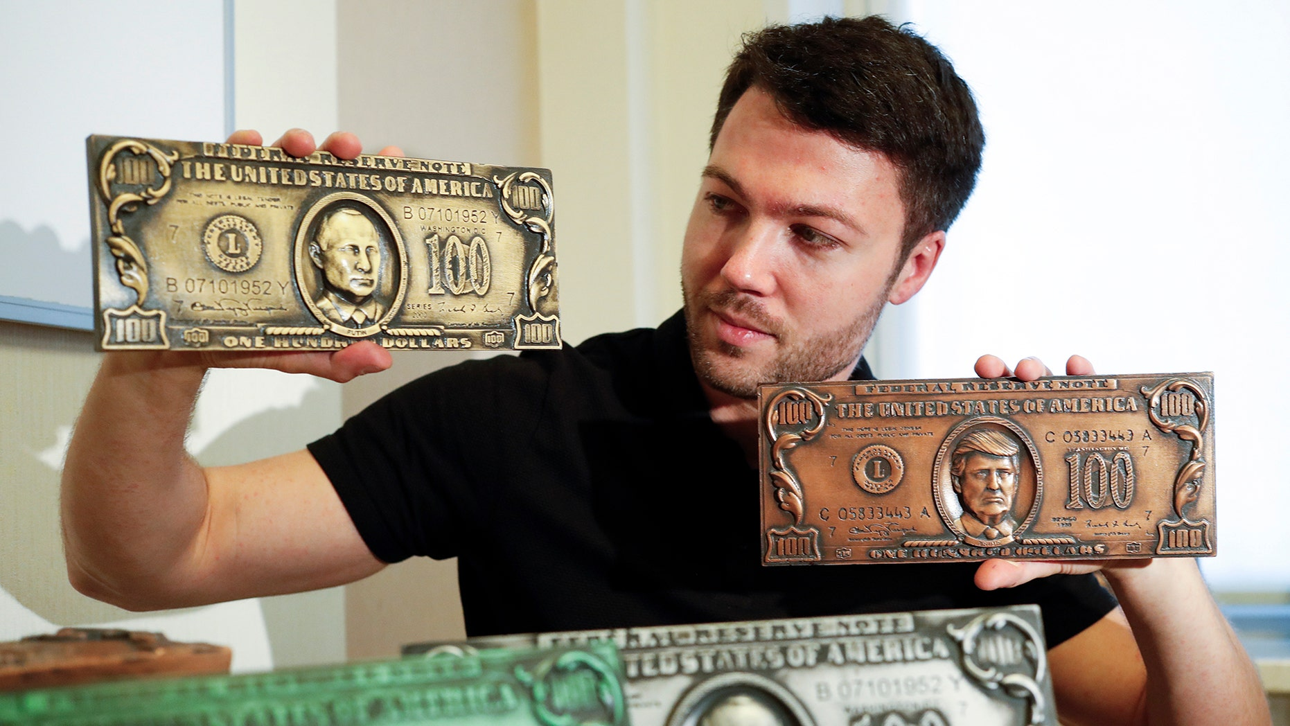 Former Russian hacker Sergey Pavlovich, better known by his former online alias Police Dog, holds mock money printing plates with Russian President Vladimir Putin, left, and US President Donald Trump faces in place of Benjamin Franklin.