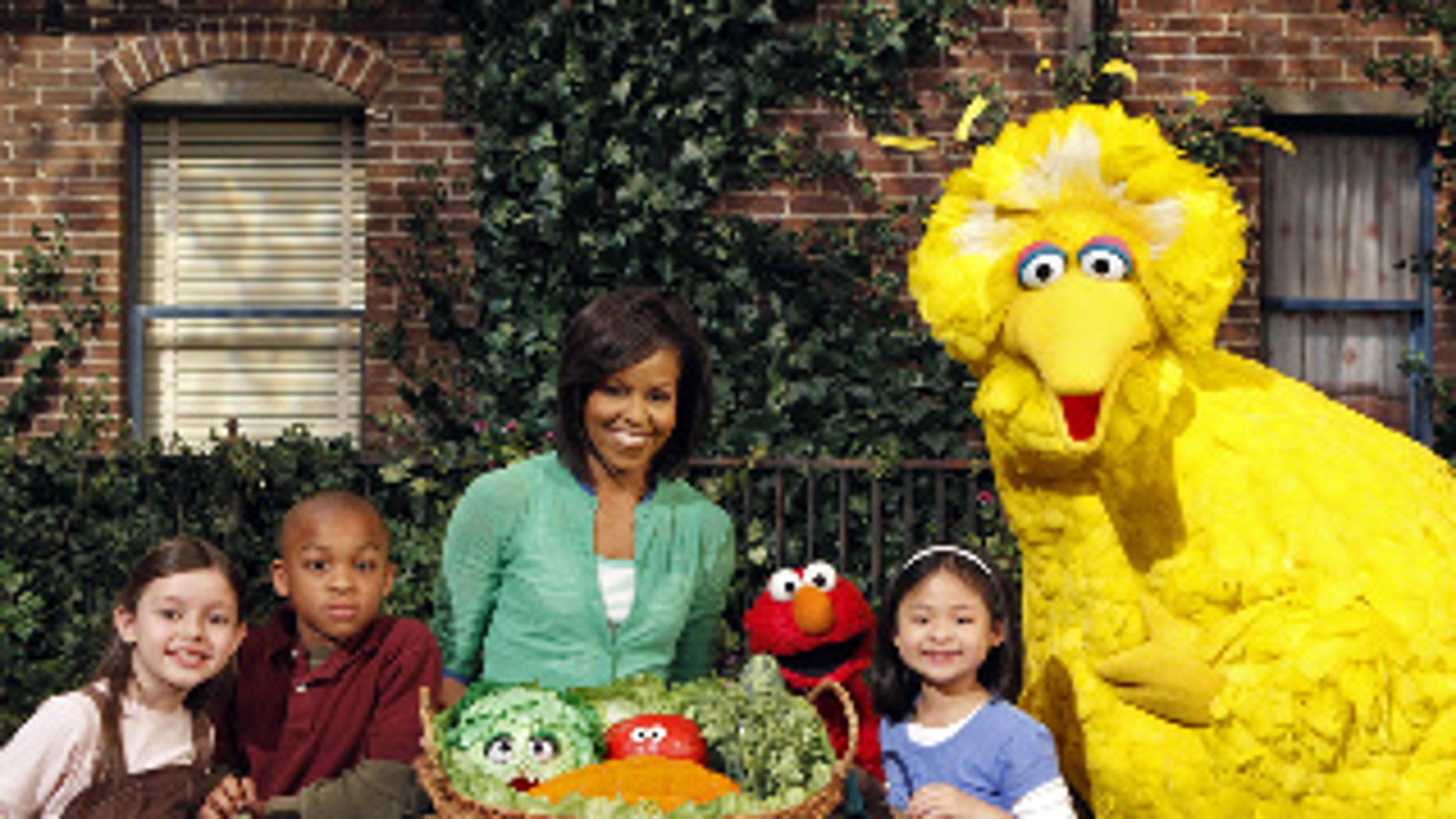 """This May 5, 2009 photo released by Sesame Workshop shows first lady Michelle Obama, third from left, with Big Bird, Elmo, Muppets & cast in """"Michelle Obama Plants A Garden"""" in Astoria, N.Y. Mrs. Obama appears on """"Sesame Street"""" Tuesday, Nov. 10, 2009, and recently taped an episode of """"Iron Chef America,"""" just two of the varied platforms she's been using lately to get her healthy-eating message out to the masses. (AP Photo/Sesame Workshop, Richard Termine)"""