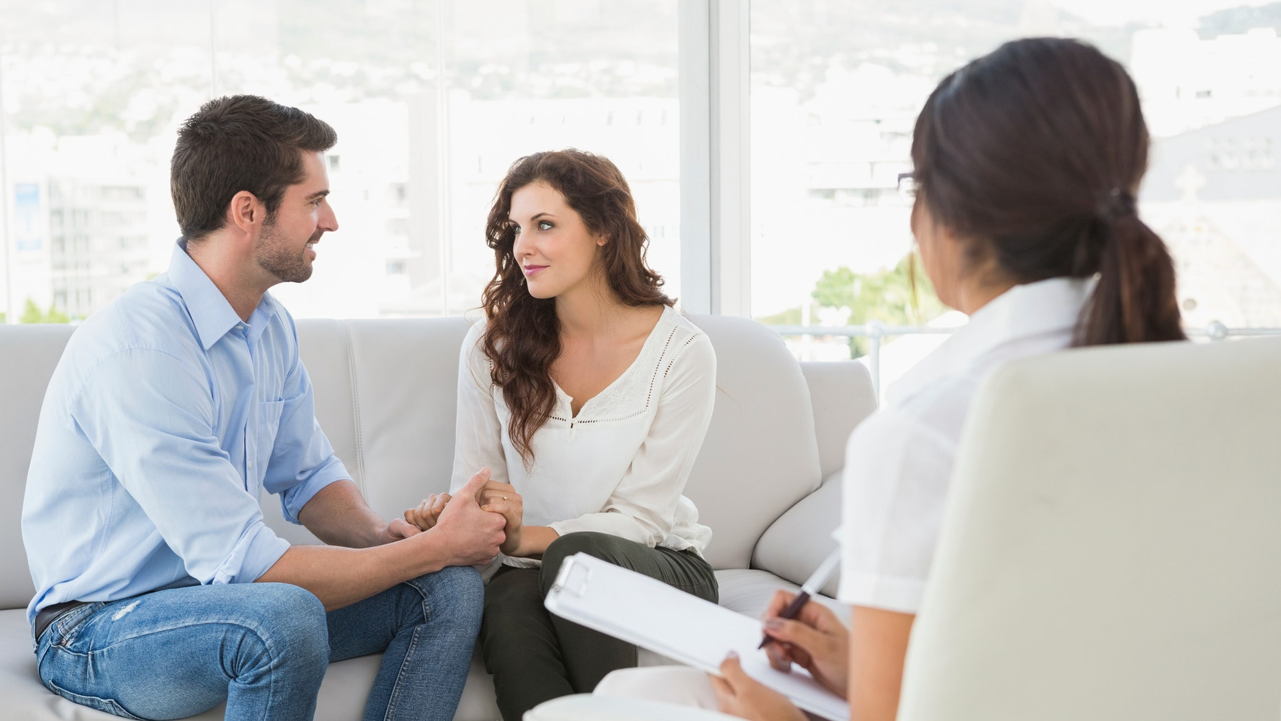 Reconciled couple smiling at each other in the therapist office