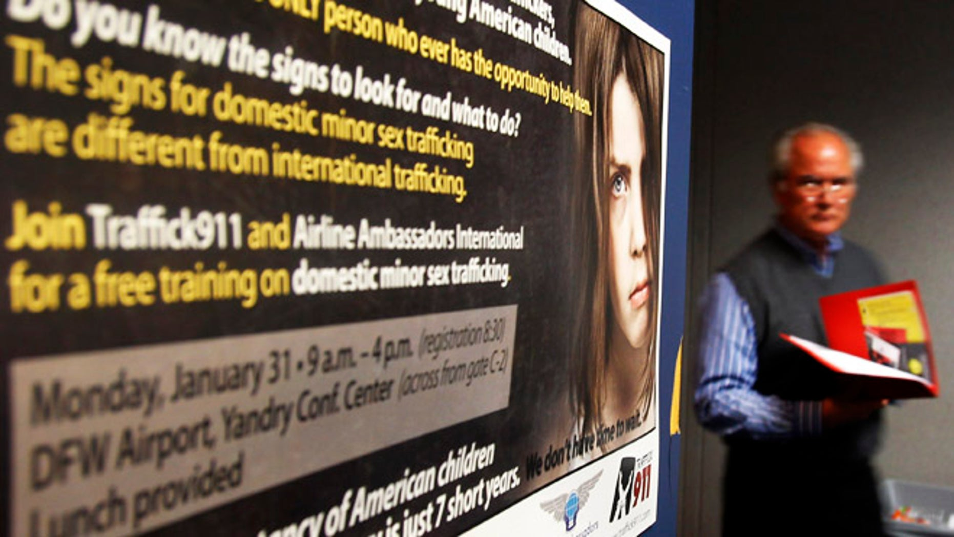 A participant in a training program walks past a poster drawing attention to sex-trafficking at Dallas Fort Worth International Airport in Dallas, Texas, January 31, 2011 ahead of NFL football's Super Bowl XLV to be played February 6.  Pimps will traffic thousands of under-age prostitutes to Texas for Sunday's Super Bowl, hoping to do business with men arriving for the big game with money to burn, child rights advocates said. REUTERS/Brian Snyder (UNITED STATES - Tags: SPORT FOOTBALL CRIME LAW SOCIETY) - RTXXC3I