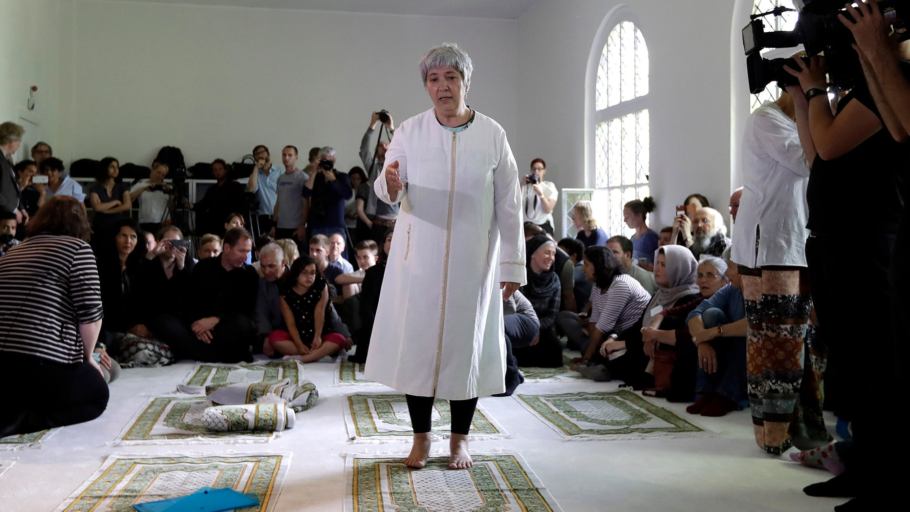 Seyran Ates, standing at center, founder of the Ibn-Rushd-Goethe-Mosque gestures during the opening of the mosque in Berlin, Germany, Friday, June 16, 2017.