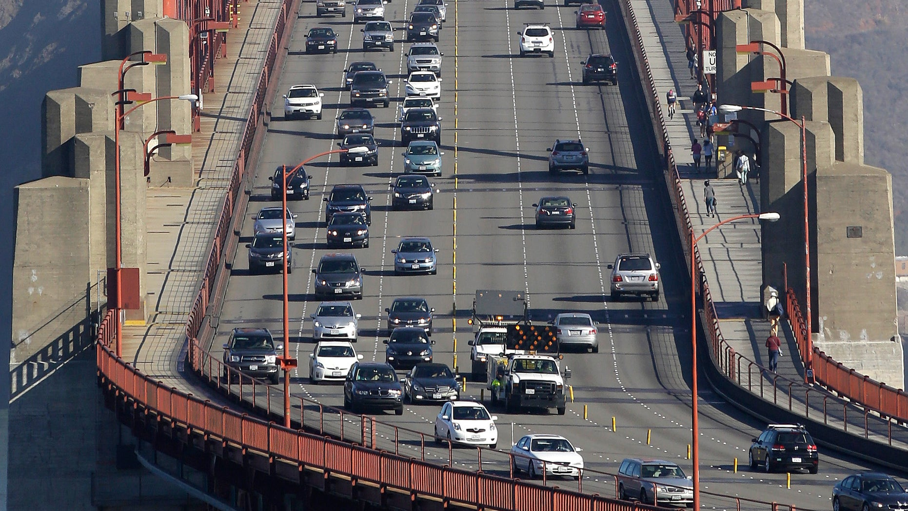 Sept. 19, 2013: Golden Gate Bridge workers shift traffic lanes during the end of the morning commute in San Francisco.