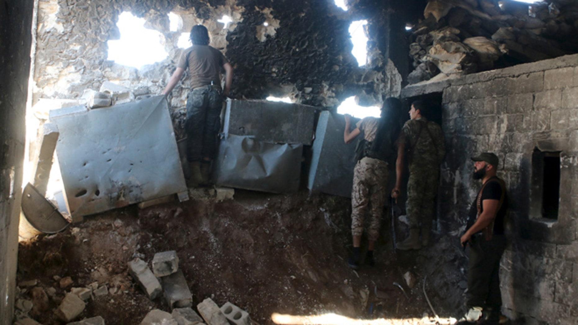 APRIL 19: Harakat Nour al-Din al-Zenki fighters look out inside a damaged building in Handarat area, north of Aleppo Syria April 19, 2016.