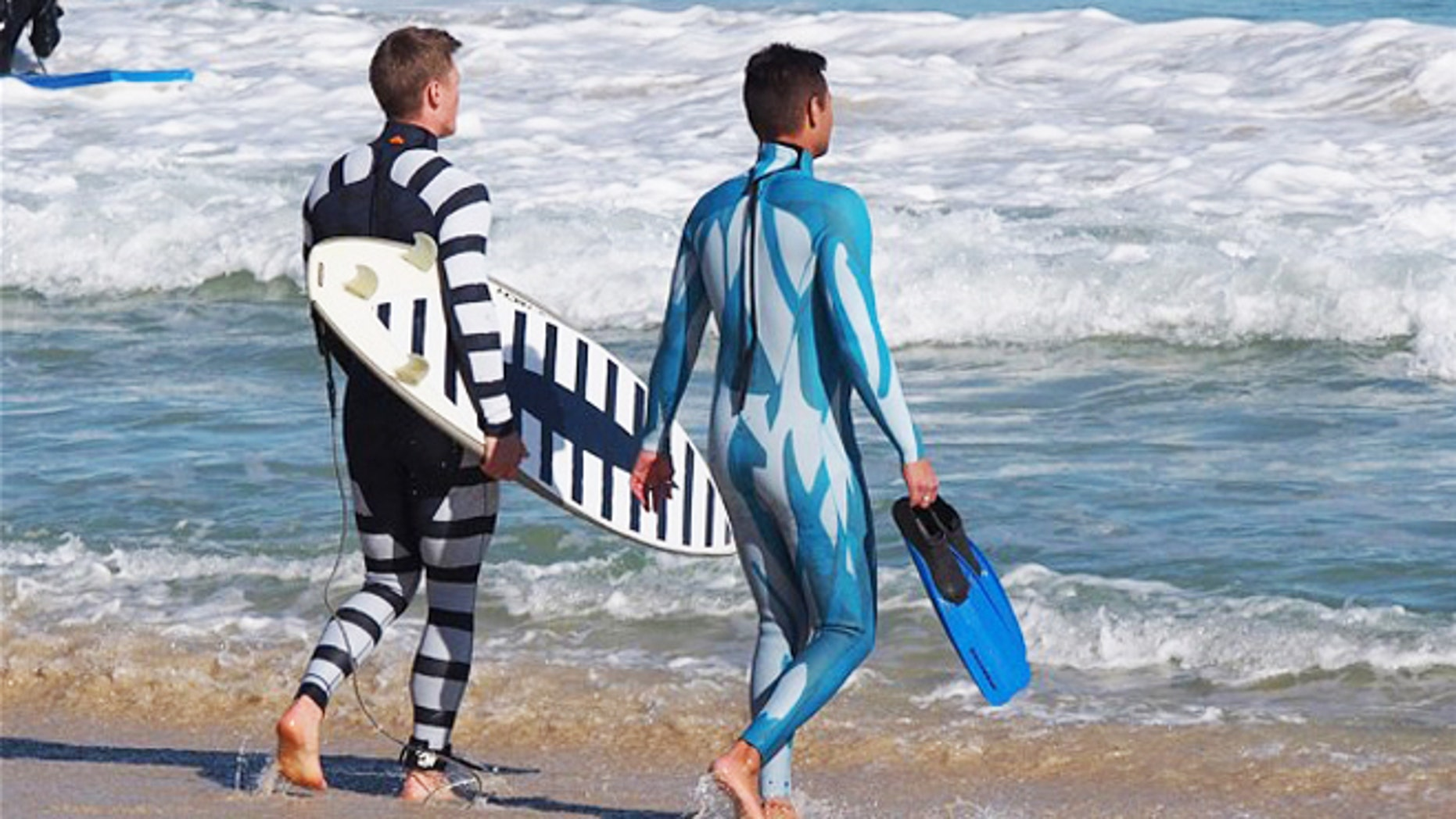 July 18, 2013: A surfer and a diver wearing wetsuits displaying the two styles of shark deterrent technology, with the surfer holding a surfboard also showing the new design.