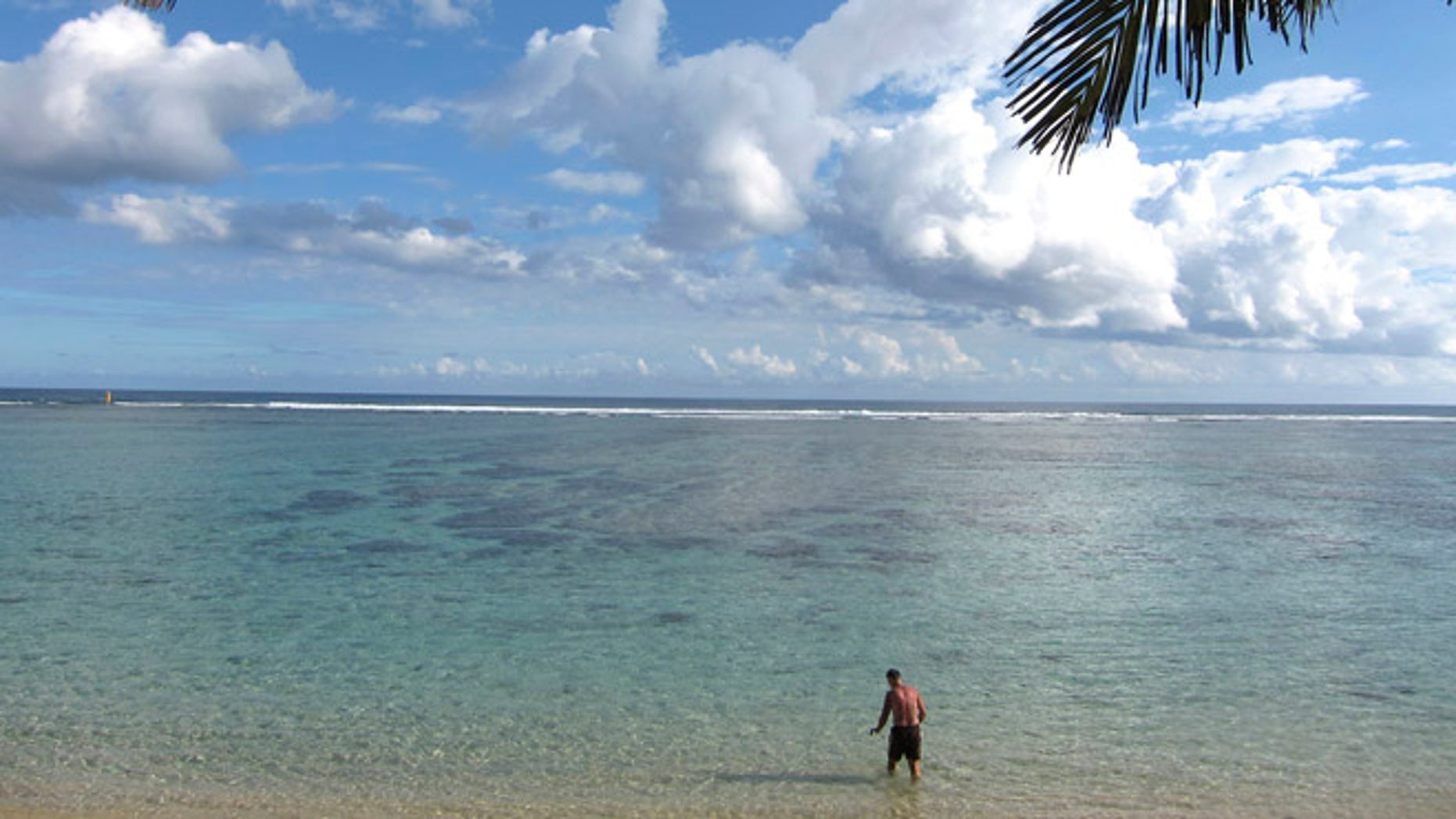 In this June 22, 2010 file photo, a man enjoys the beach of Saint Paul, northwest of the Reunion  island, a French oversea territory in the Indian Ocean. Authorities on the island say a 15-year-old girl was killed Monday July 15, 2013 by a shark as she swam just a few meters from the shore in Saint-Paul. While the French island has seen occasional attacks on surfers farther out from shore, officials say attacks on swimmers close to shore are exceedingly rare.