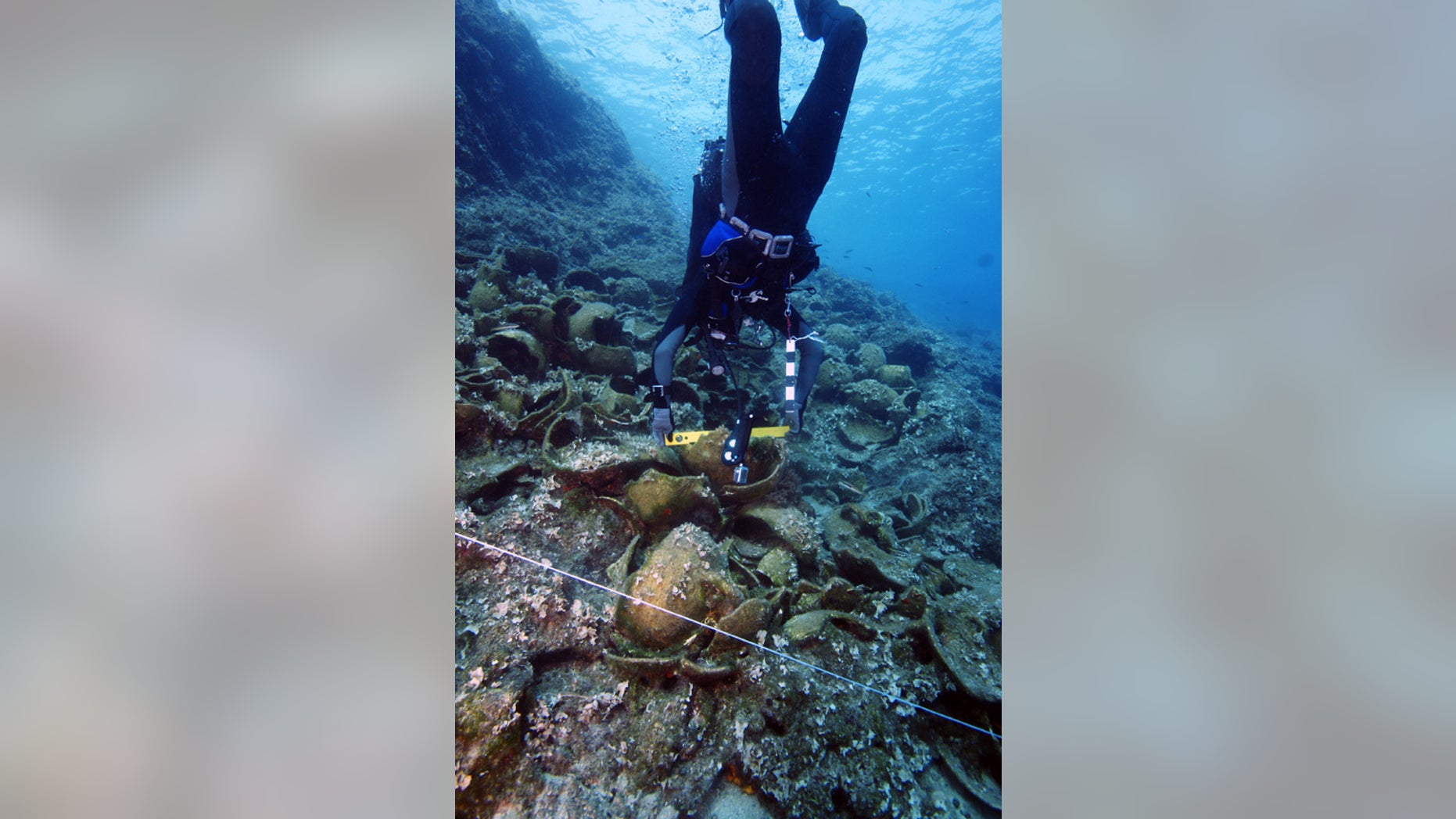 An archaeologist prepares a level on one of the wrecks.