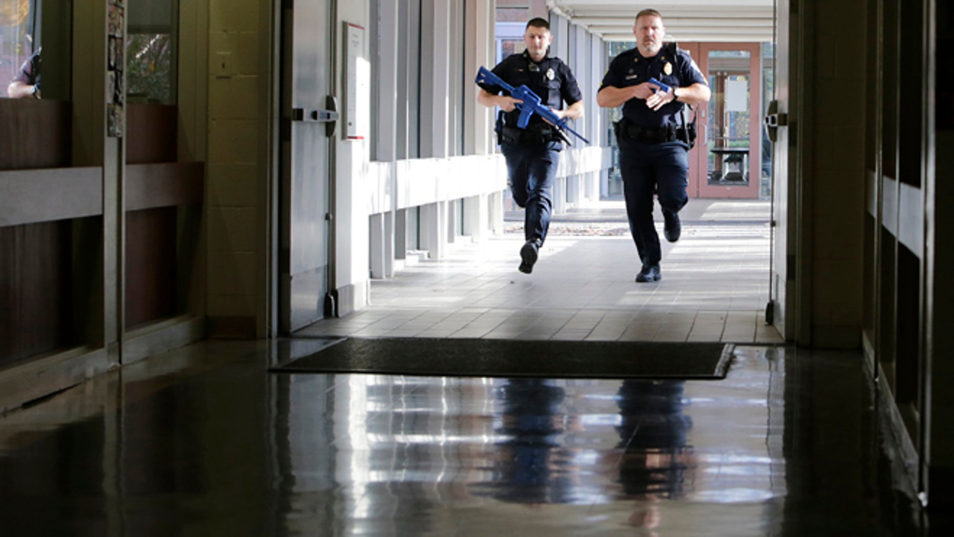 Officers from the Methuen, Mass., police department carry training weapons as they search the halls of a school during a demonstration in Methuen, Tuesday, Nov. 11, 2014. School and police officials have unveiled a new system to detect and track a gunman that they say is the first in operation in a public school. (AP Photo/Charles Krupa)