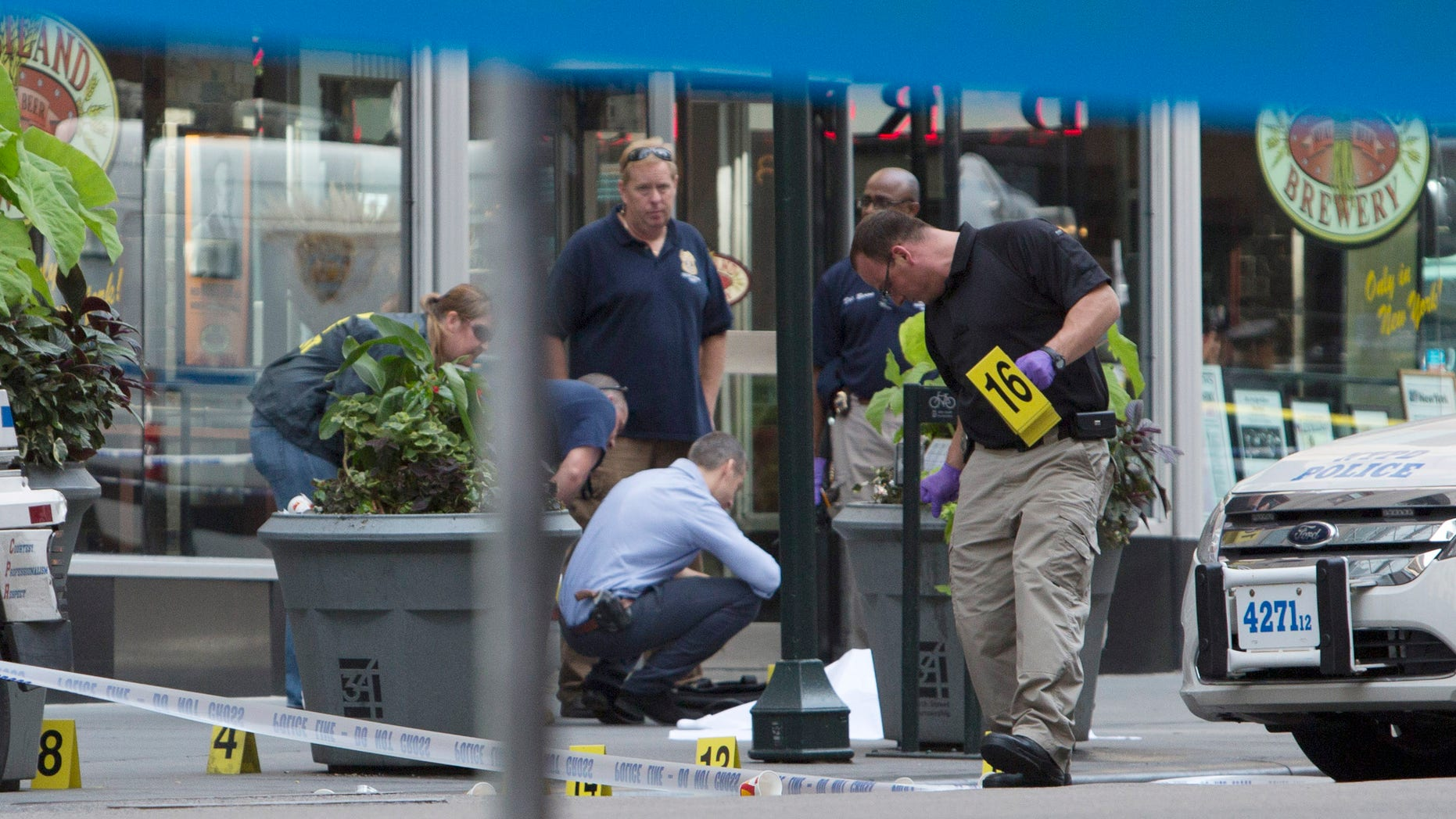 New York Police mark bullet casings beside the body of 58-year-old Jeffrey Johnson near the Empire State Building August 24, 2012 in New York City.