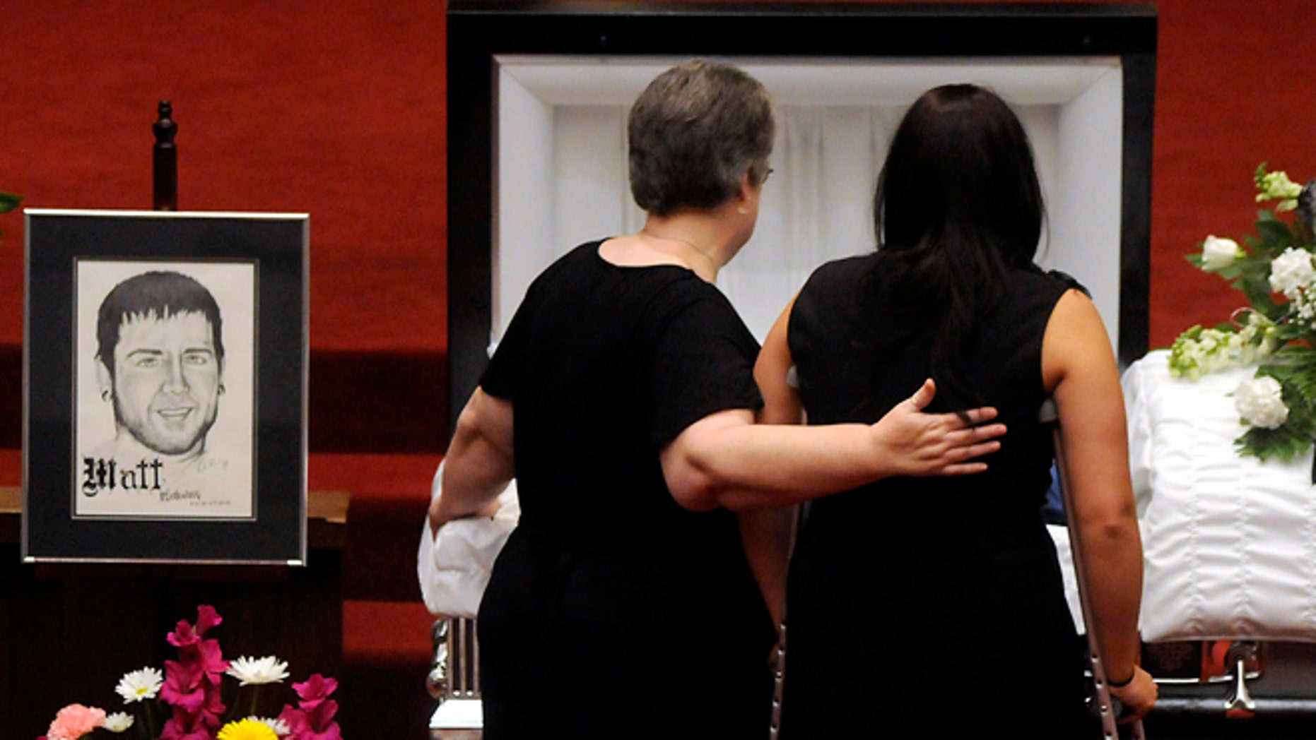 July 28, 2012: Samantha Yowler, right, pays her final respects to boyfriend Matt McQuinn, at the Maiden Lane Church of God, in Springfield, Ohio. McQuinn shielded his girlfriend, Yowler, from gunfire during the shooting at the Aurora, Colo., movie theater on July 20.