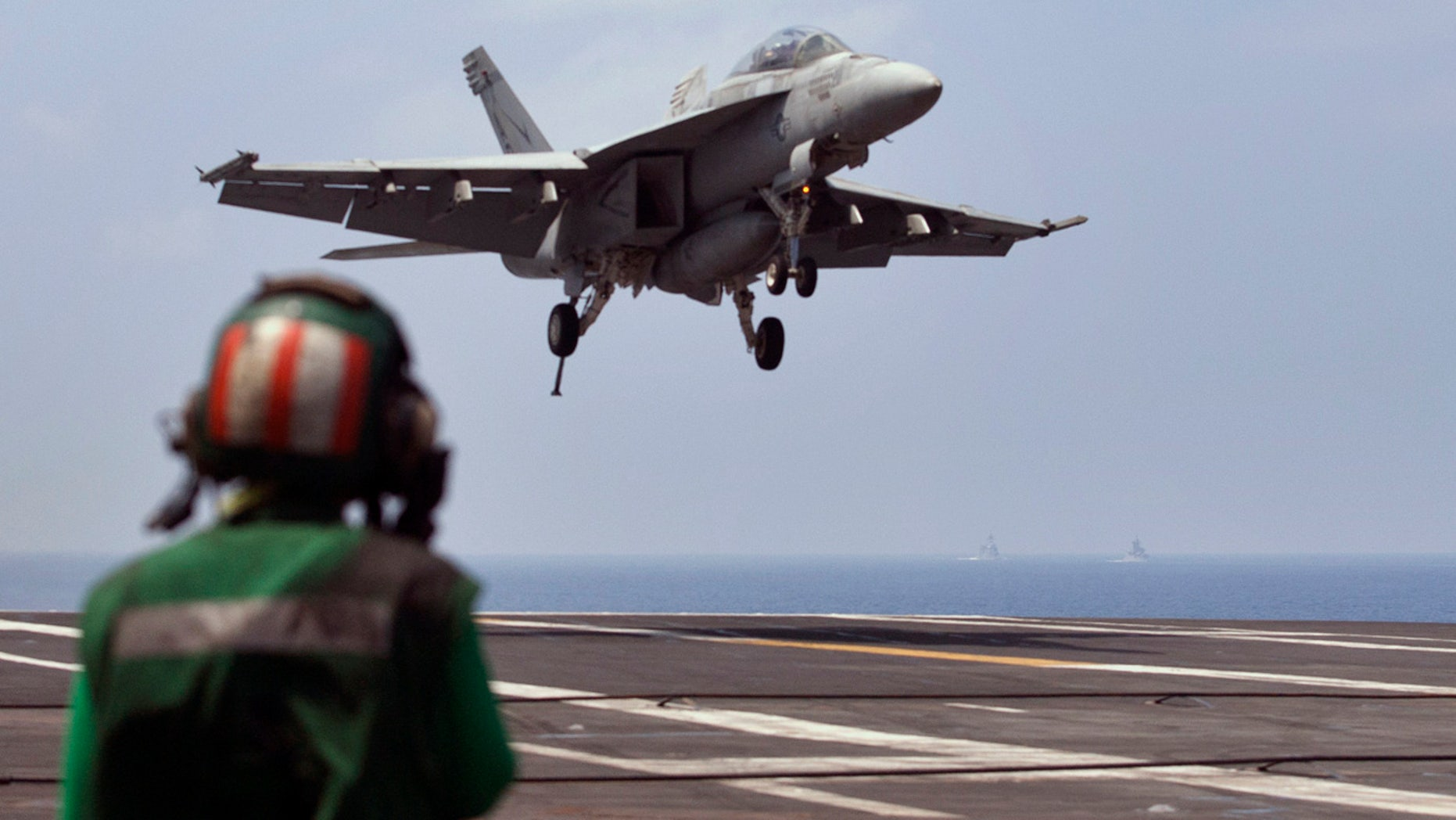FILE - This Oct. 17, 2015 file photo shows a U.S. Navy fighter jet approaching to land on the U.S. Navy aircraft carrier USS Theodore Roosevelt during Exercise Malabar 2015 about 150 miles off Chennai, India. (AP Photo/Arun Sankar K., File)