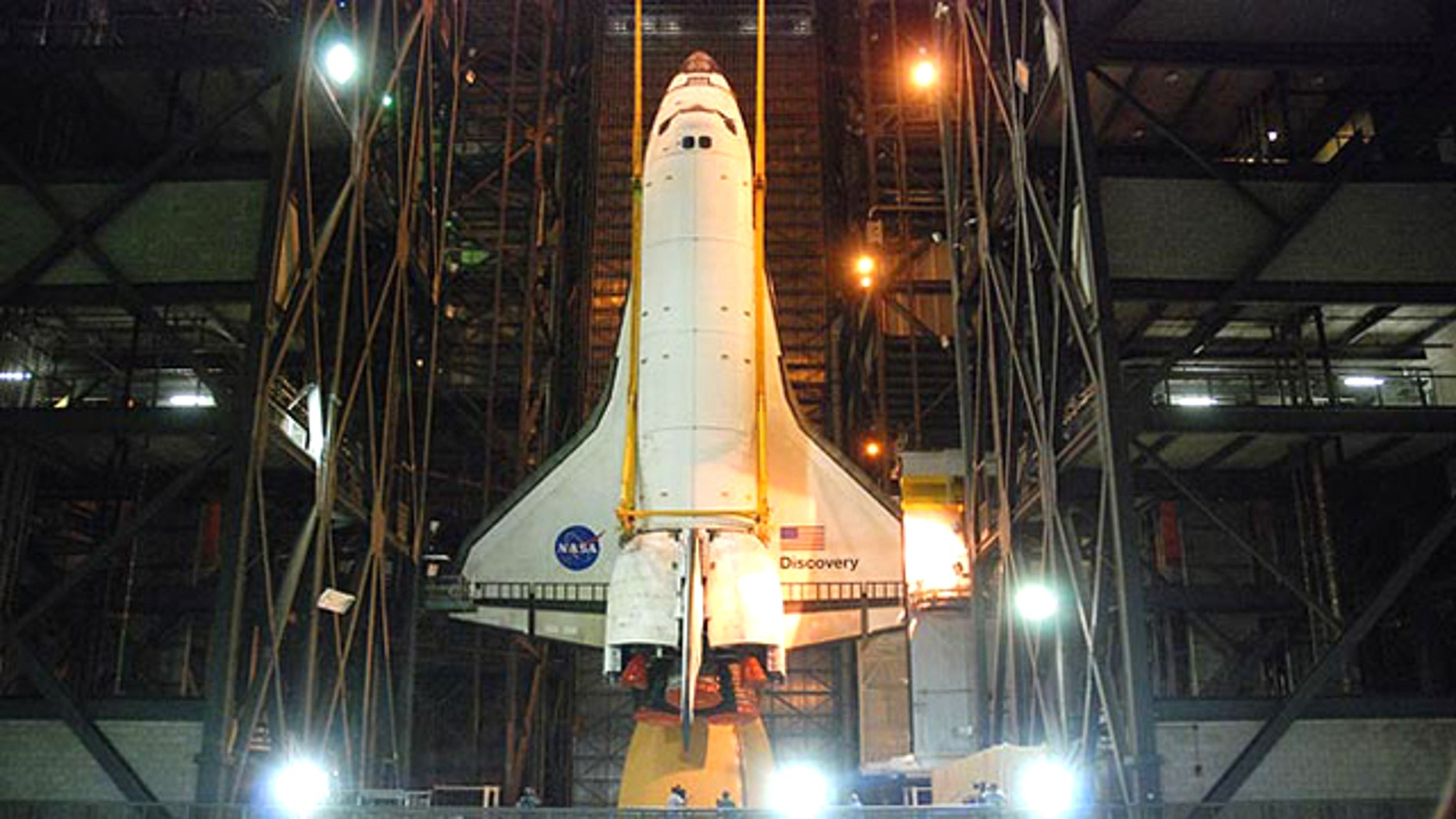 Space shuttle Discovery is hoisted into position to be attached to its external tank and solid rocket boosters for its final launch into space on the STS-133 mission to the International Space Station.