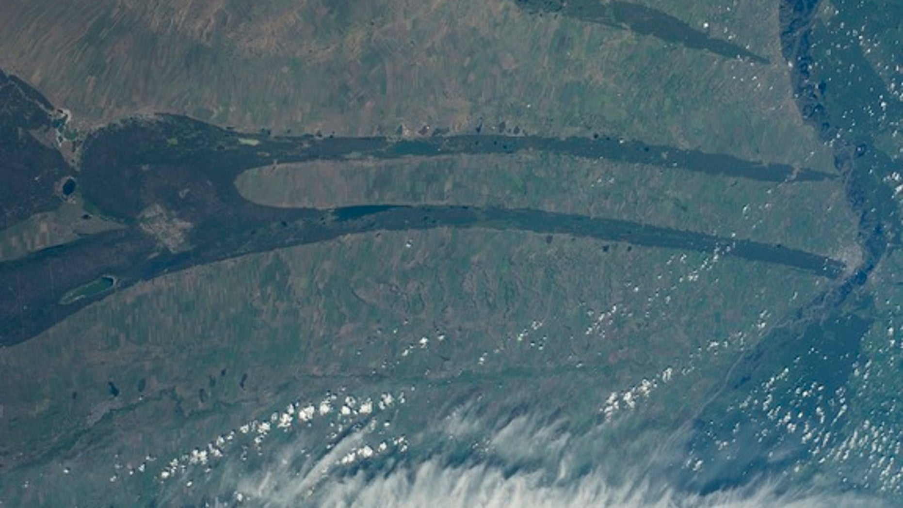 Strange spiky shapes slash across the Kulundra Steppe of Siberia in an astronaut photograph snapped from the International Space Station in June 2014. From left to right, this image covers about 185 miles (300 kilometers) of ground.