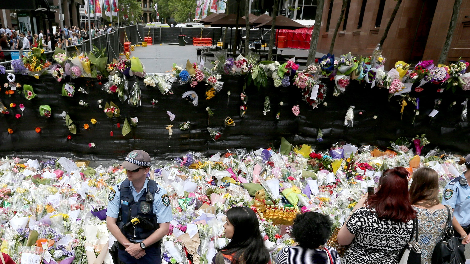Dec. 17, 2014: Police stand watch over flower tributes to the shooting victims on the footpath outside the the cordoned off area outside the Lindt cafe in the central business district of Sydney.