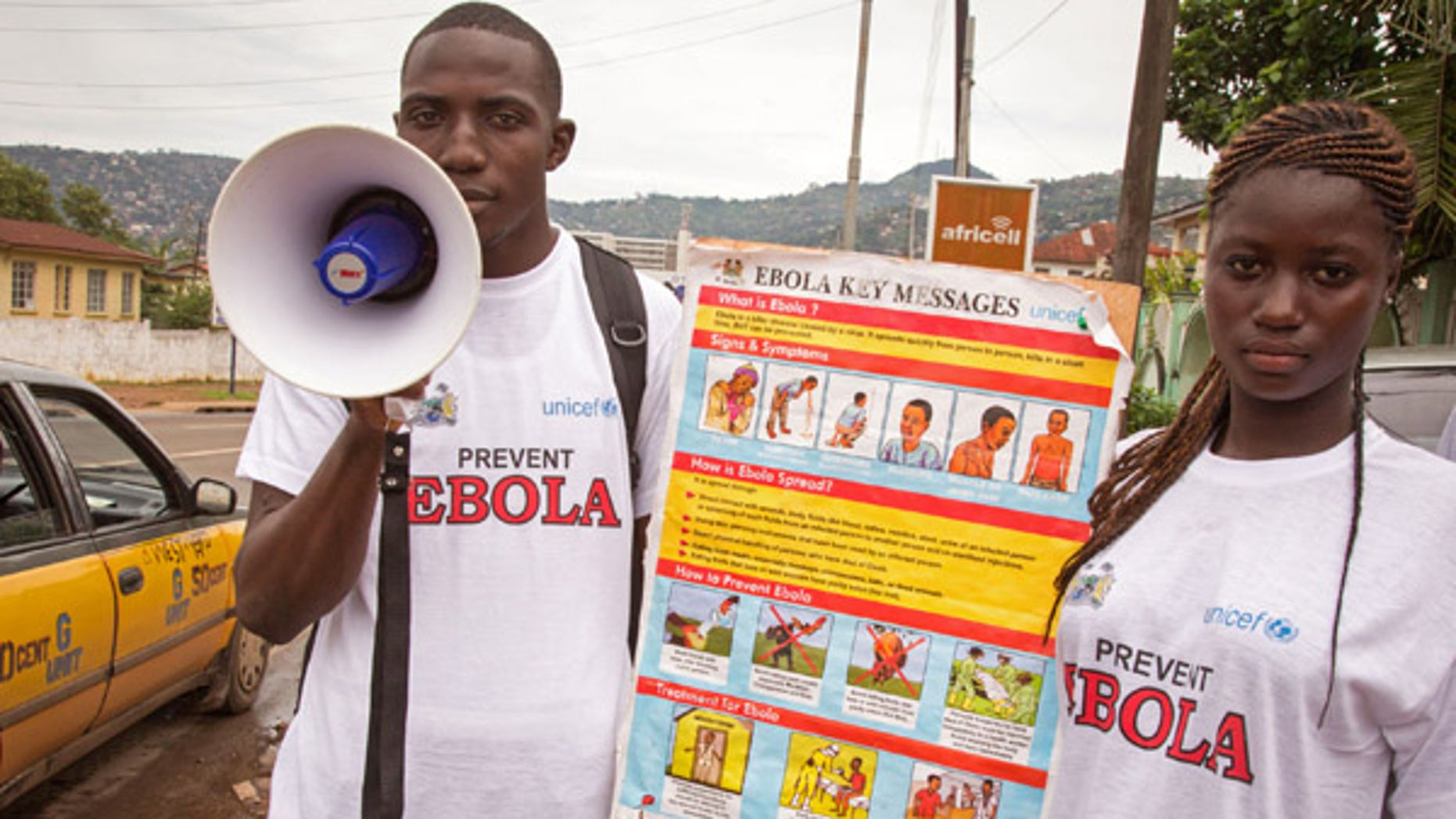 Aug. 6, 2014: A man and woman taking part in a Ebola prevention campaign holds a placard with an Ebola prevention information message in the city of Freetown, Sierra Leone.