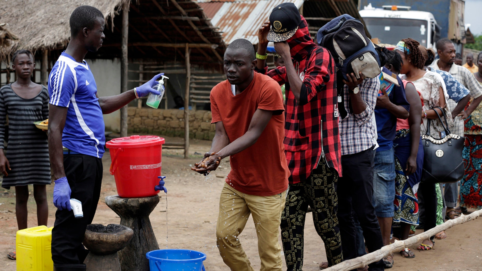 FILE-In this file photo taken Wednesday, Aug. 12, 2015, a man checks people's temperature and helps to wash their hands as they leave an Ebola quarantined area on the outskirts of Freetown, Sierra Leone. (AP Photo/Sunday Alamba, File)