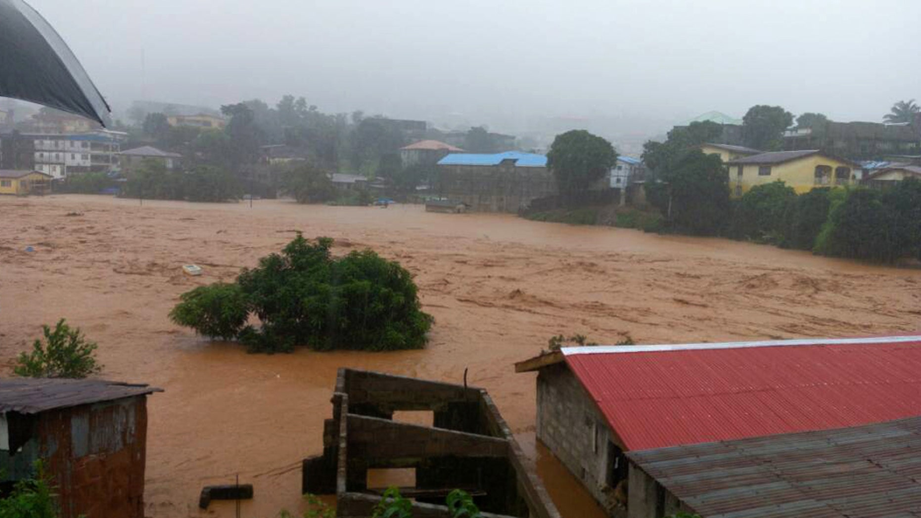 In this image made available by Society 4 Climate Change Communication, Sierra Leone, mud and water flow in Freetown Sierra Leone Monday Aug. 14, 2017.