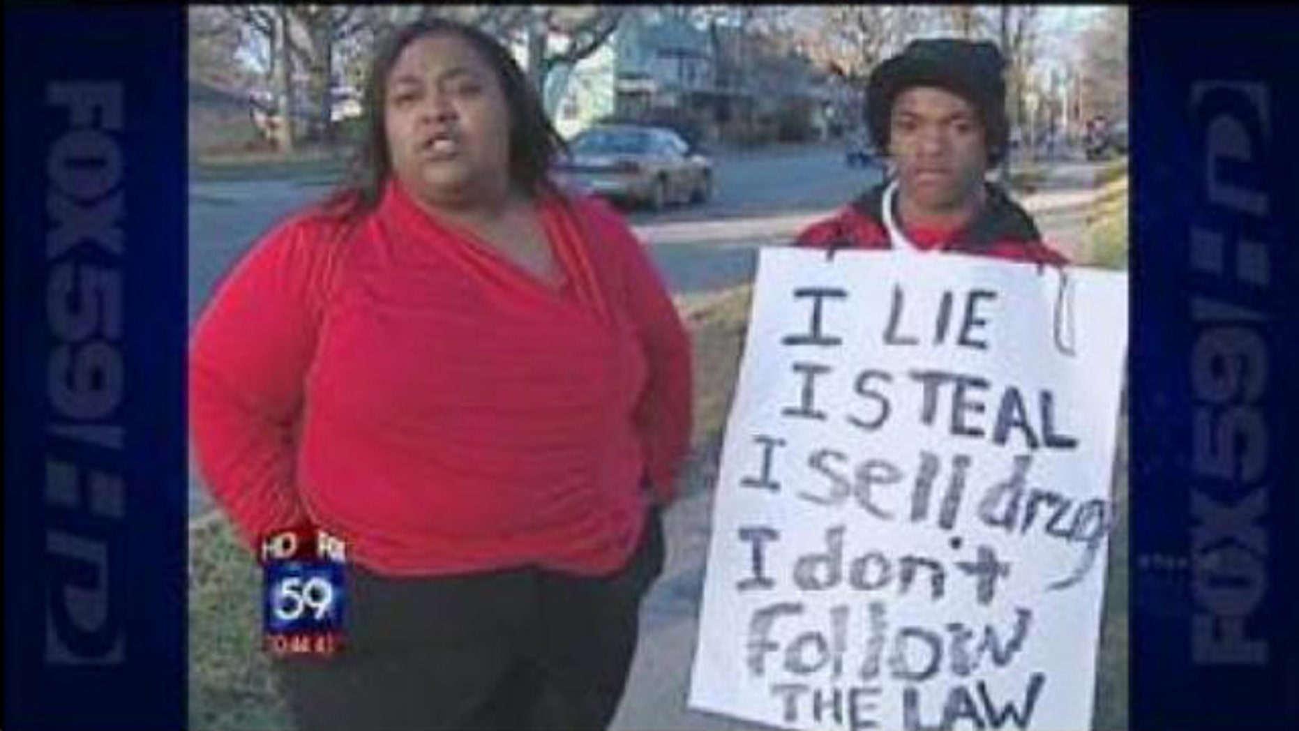 Dynesha Lax, left, forced her 14-year-old son to wear the sign on a street corner.